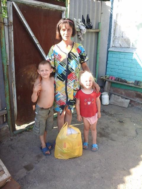 Ukrainian mother and children receiving food donations