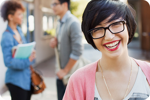 Smiling woman in glass and red lipstick outside posing for the camera. There are two blurred images of individuals (man and woman) speaking to one another . The woman his holding a few books and a book bag.