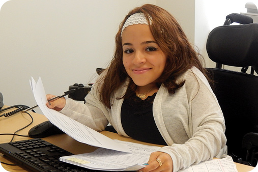 Woman on a wheelchair doing office work and smiling at the camera.