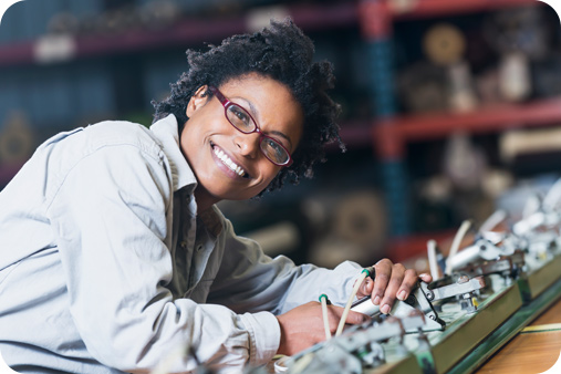 Women wearing glasses and smiling while leaning over some mechanical work she is completing.