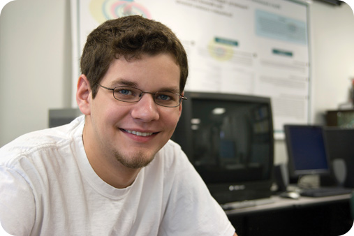 Male student in glasses sitting down and smiling.