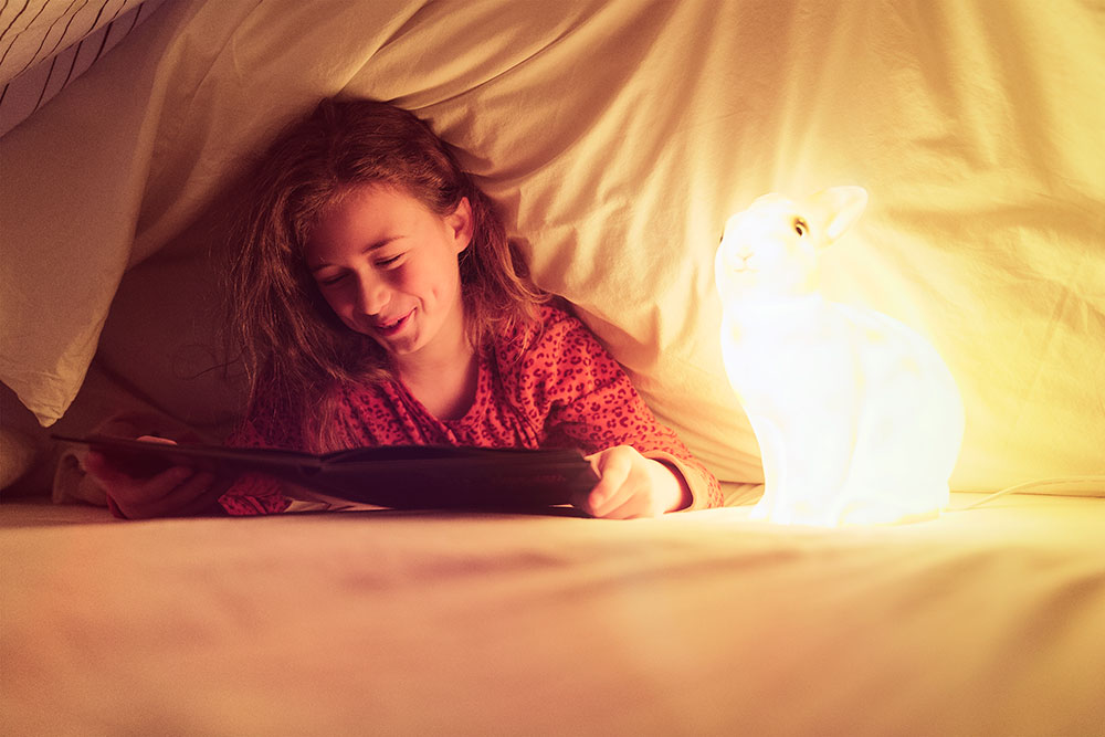 Girl reading a book under the bed cover