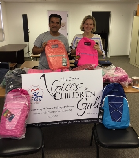 Executive Director Erica Fischer-Kaslander accepts backpacks from Ciro Callegari of Our Way to HOPE.