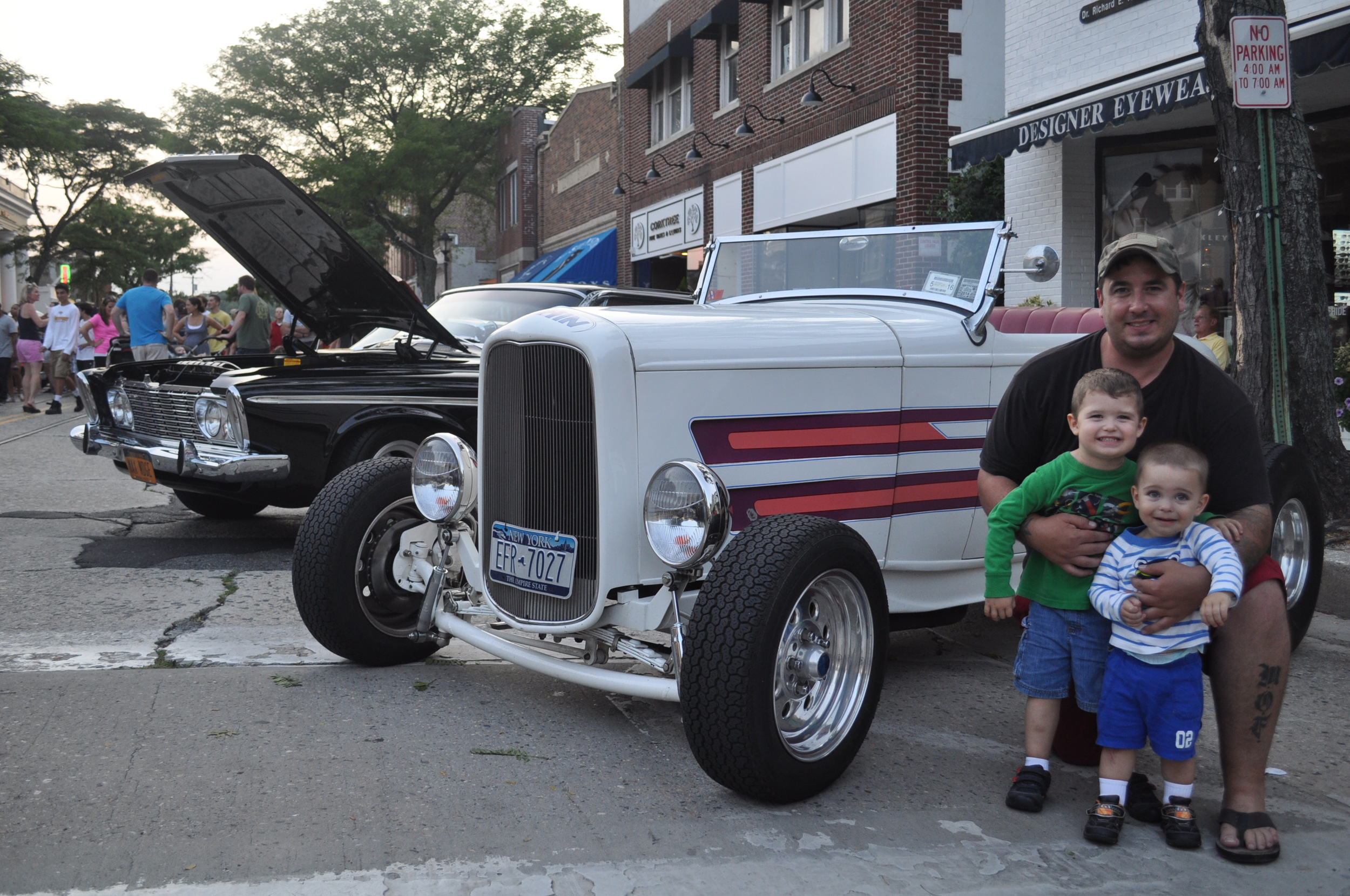 Jesse Quinn Sr., of Huntington, joins his sons, Gavin and Jesse Jr. by a vintage Ford hotrod – one of dozens of classic cars on display.
