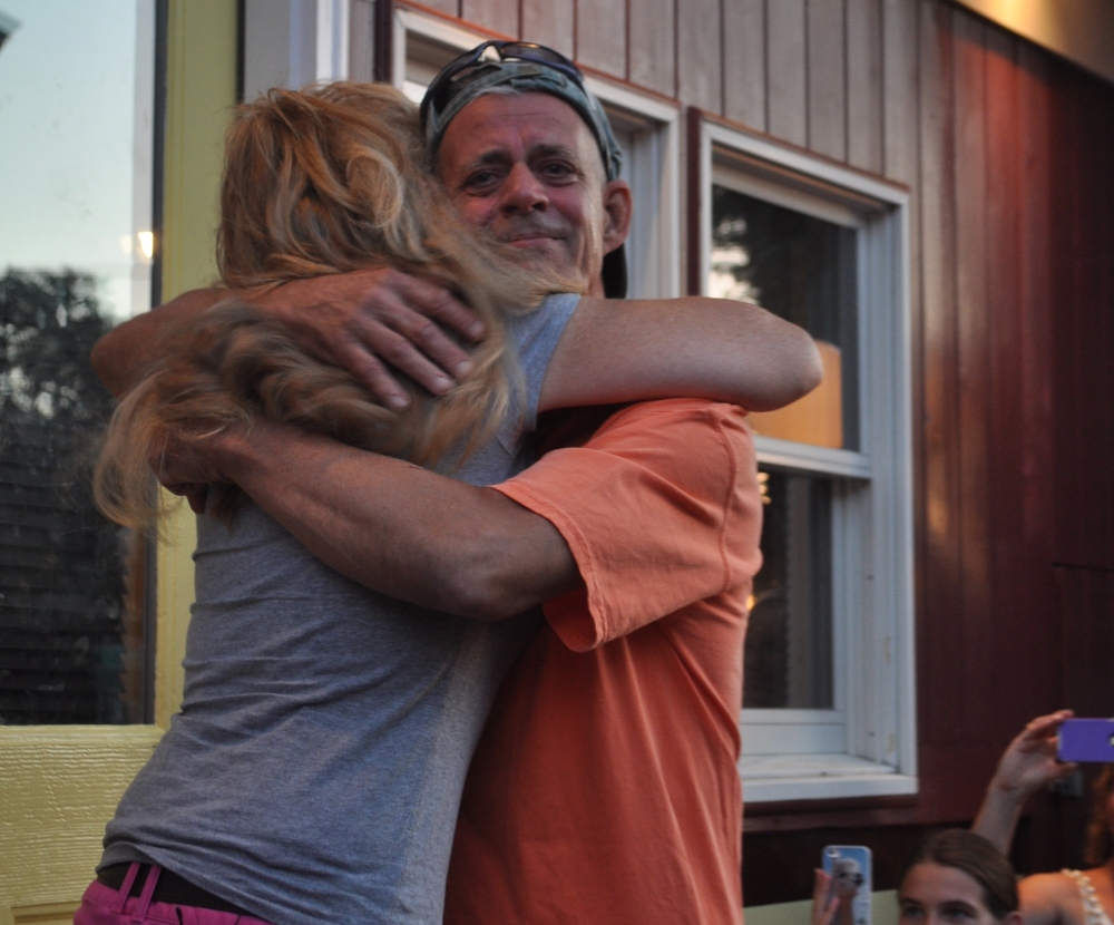 Tim Hess and Janet Eckel embrace on the front step of the Shipwreck Diner.
