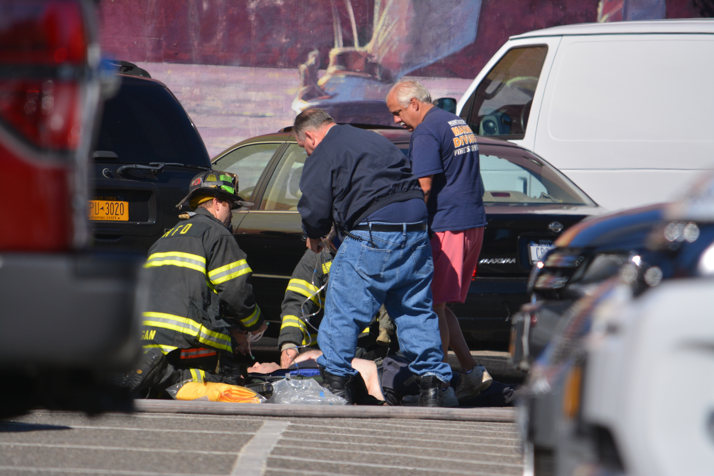 First responders treat Ralph Colamussi in a Huntington parking lot after an apparent suicide attempt, police sources confirmed. (Long Islander News photo/Arielle Dollinger)