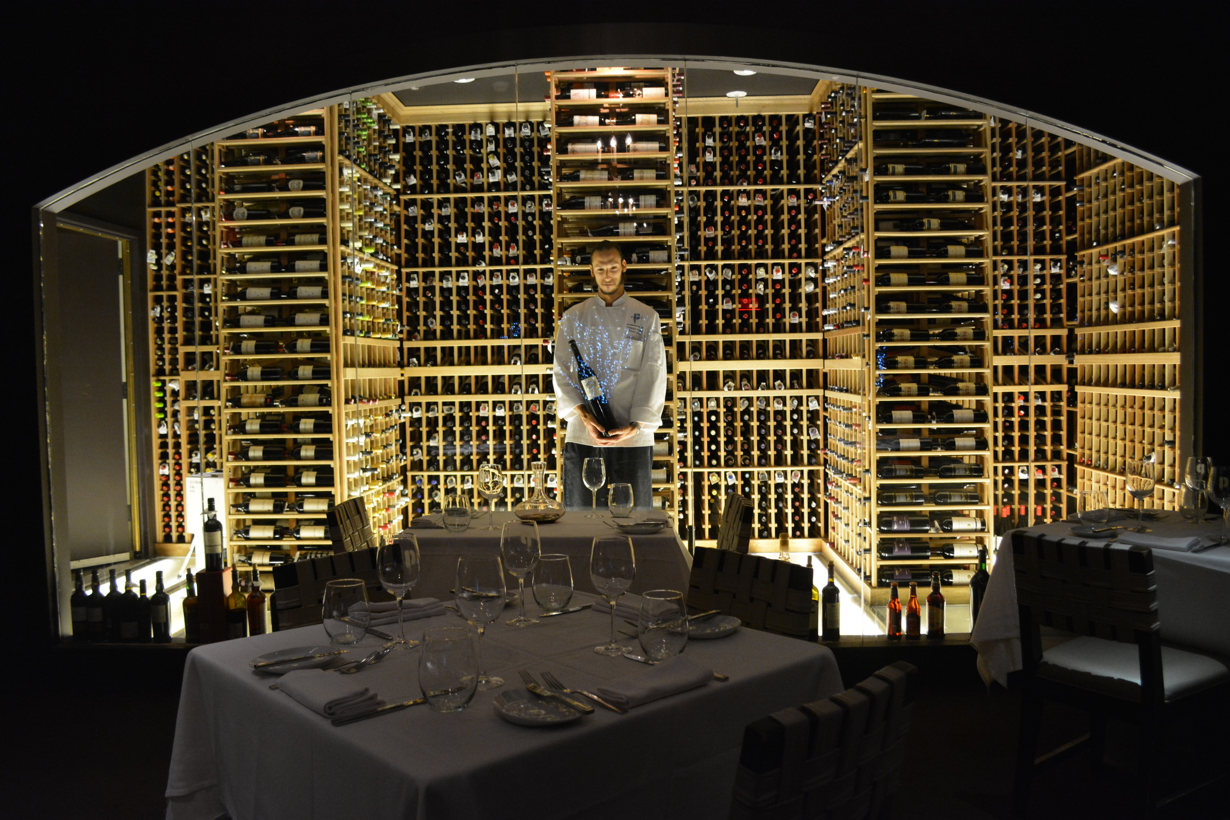 Sous Chef Franco Pollini stands in a room filled with wine, lit from the floor.