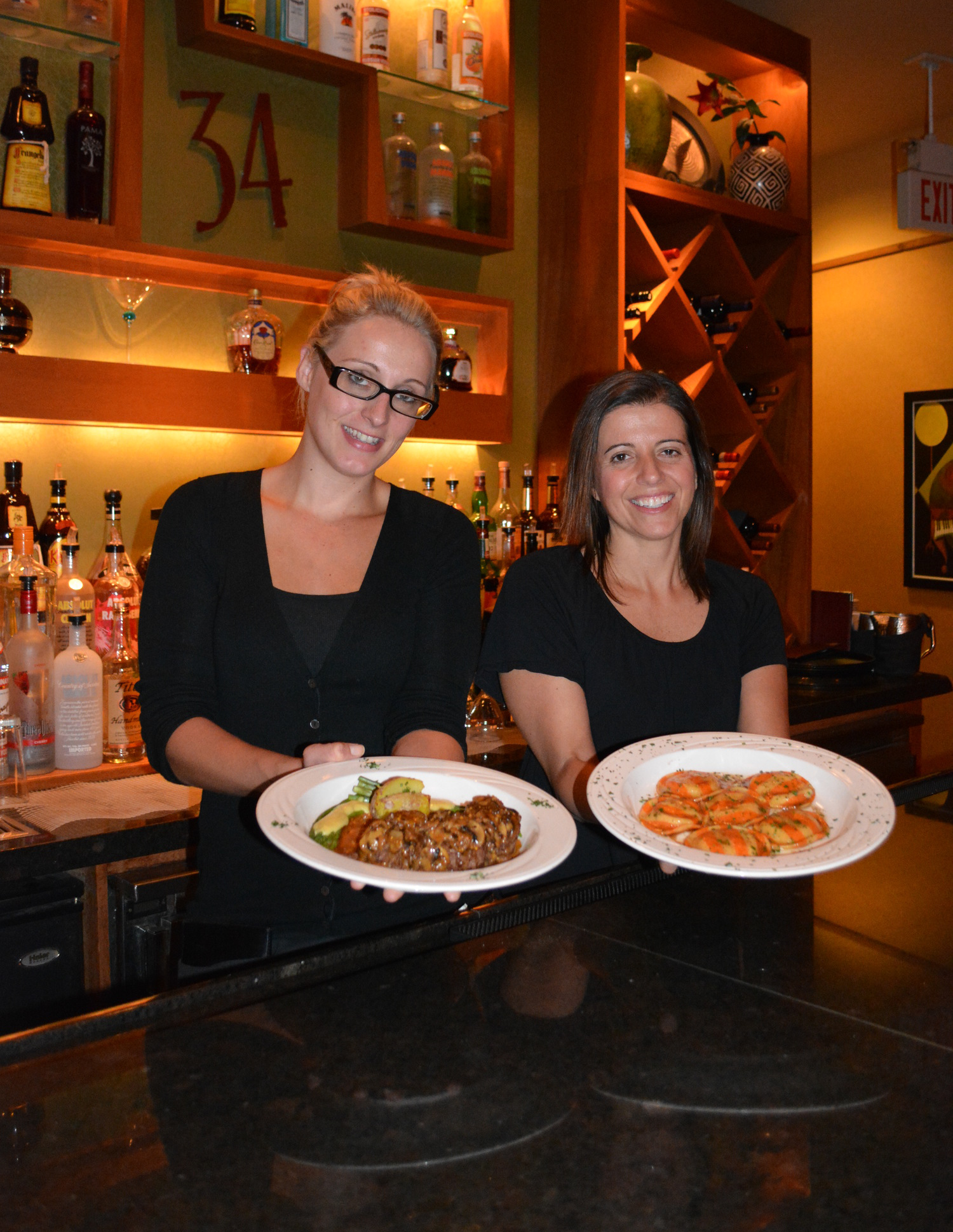 From left, waitress Alexa Pryor and manager Lisa Hockney respectively display Steak Medallions in Marsala Cream Sauce and Pumpkin Ravioli at 34 New Street, known for its creative world cuisine.