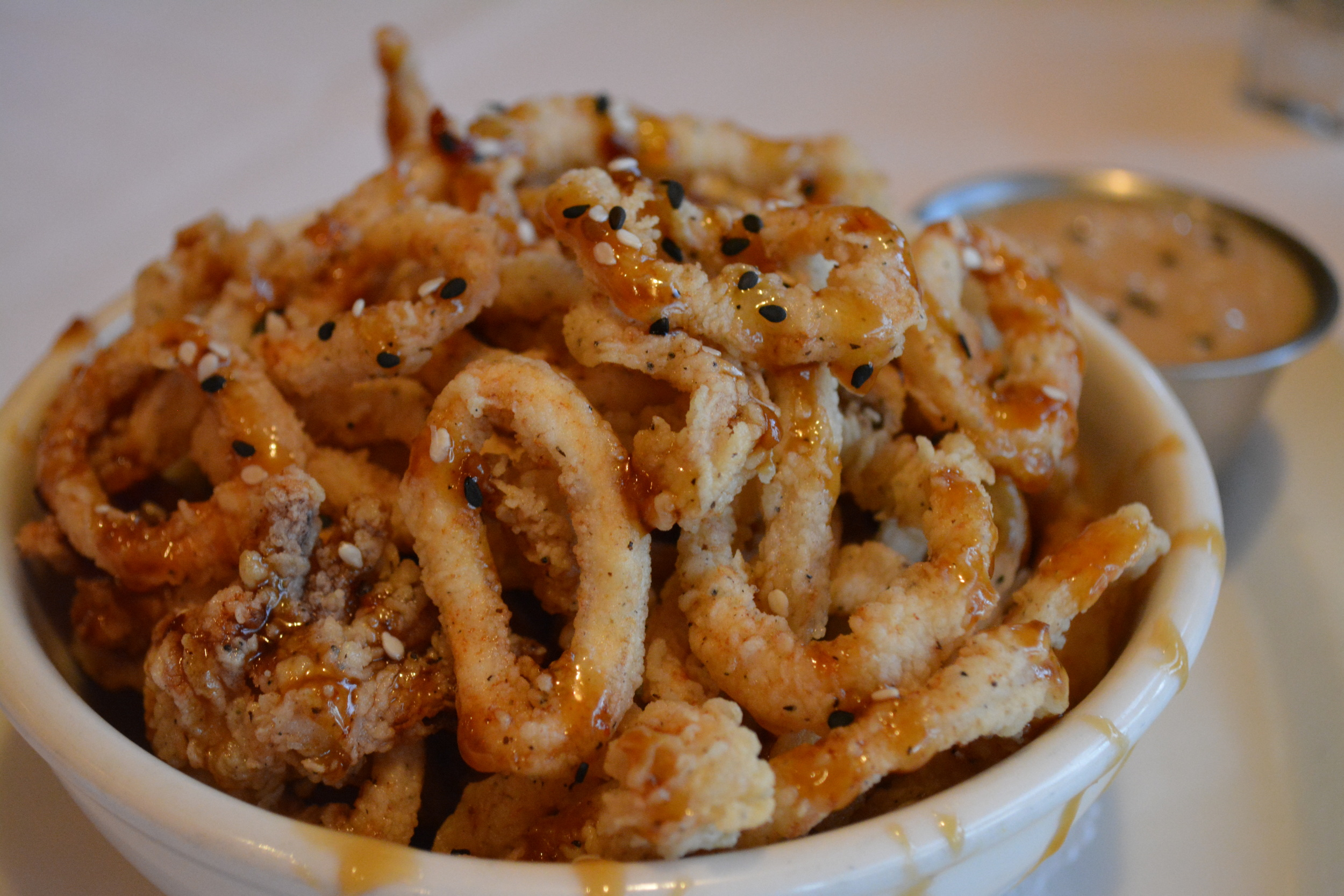 There's a nice crisp and kick to thin-sliced orange-sesame calamari.