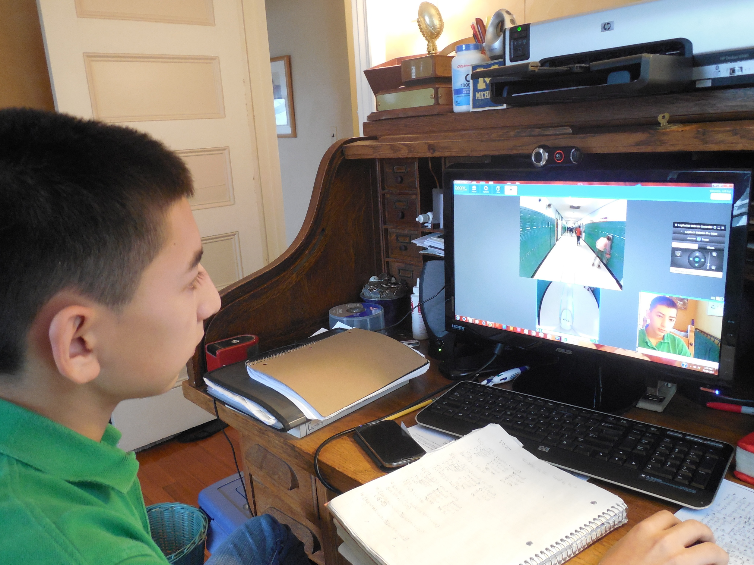 Jeffrey Kaji can see the school hallways via the robot's video camera, as he sits at home.