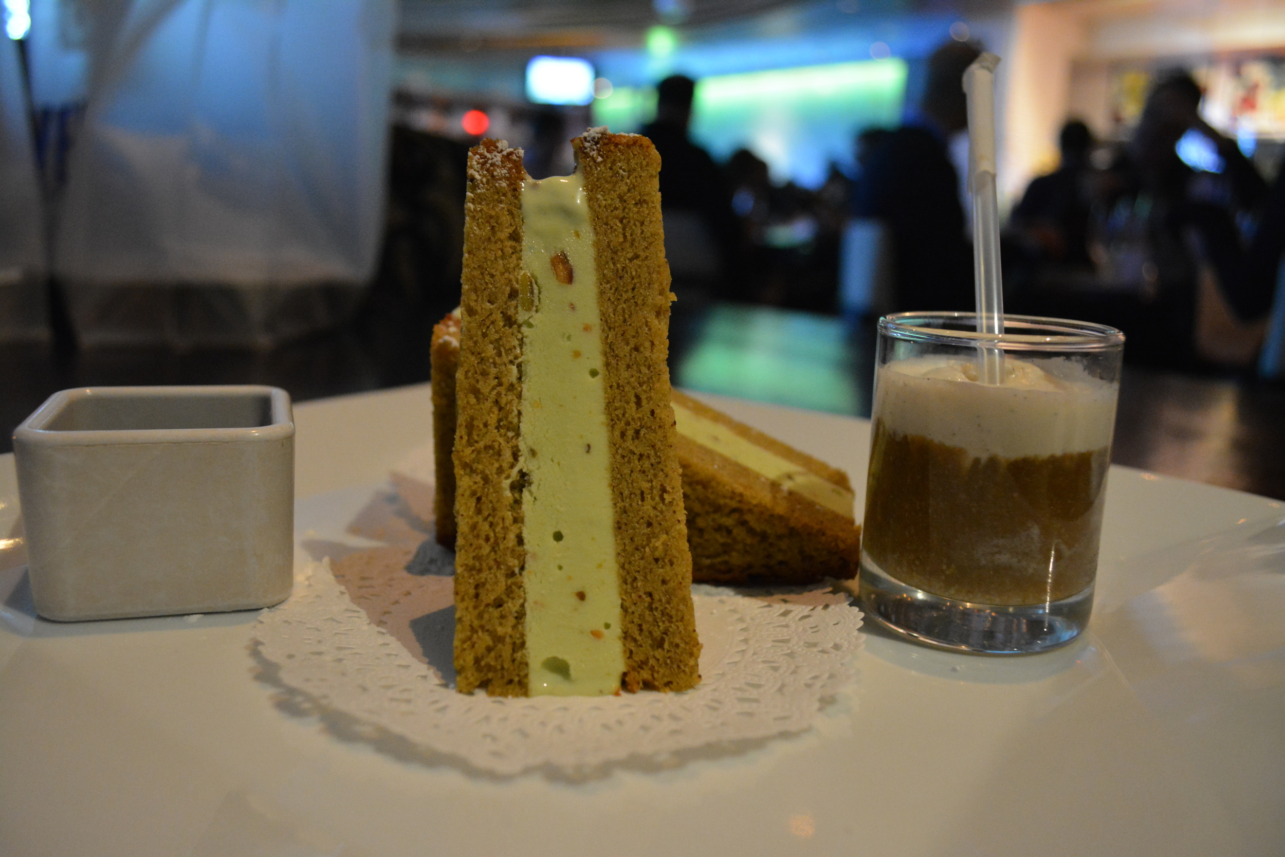 Pistachio gelato sandwiched between slices of pistachio cake is plated with a tiny root beer float.