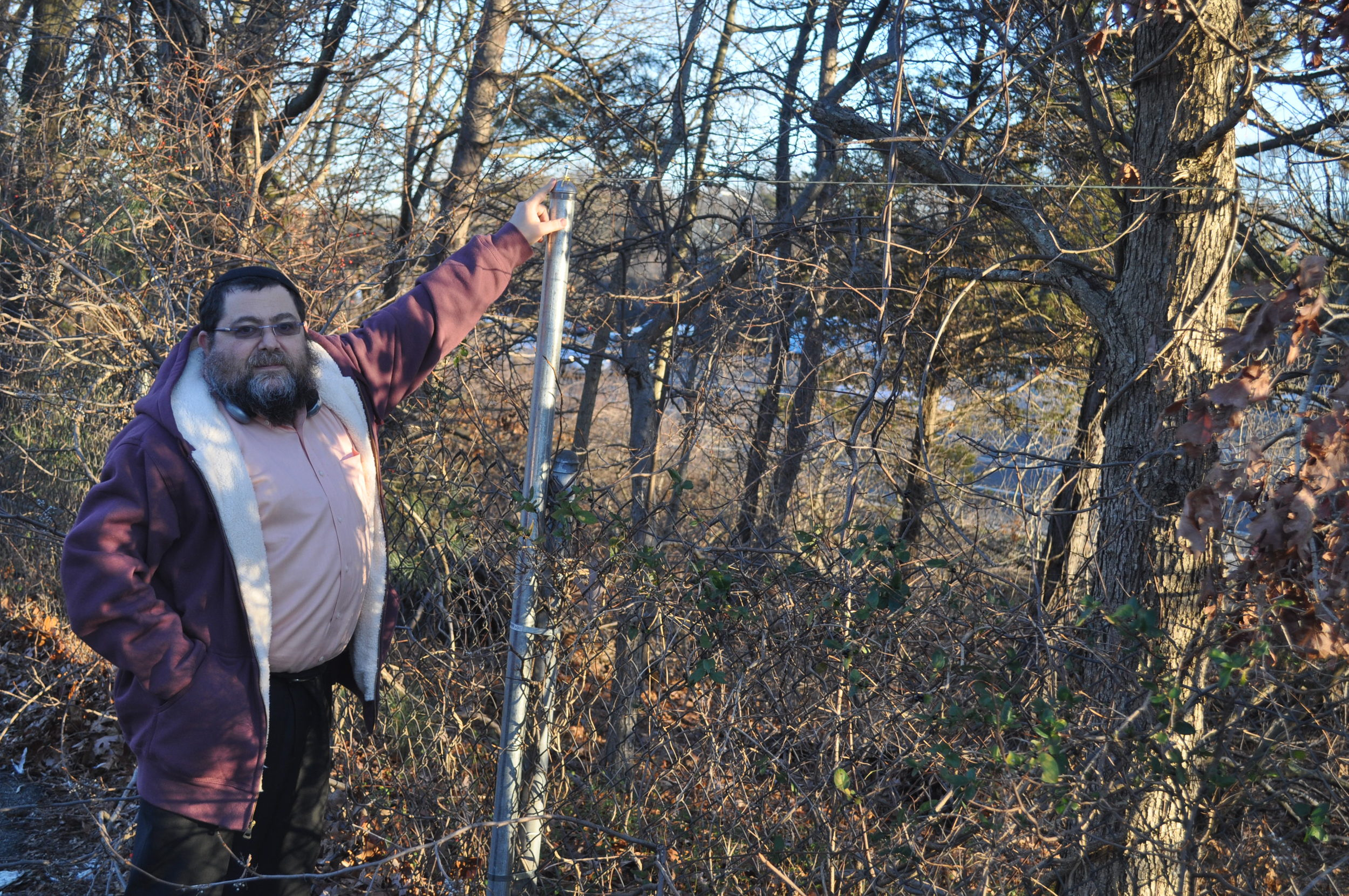 Rabbi Yaakov Saacks points out a portion of the newly constituted eruv in Dix Hills completed by stringing fishing wire to complete the unbroken link.