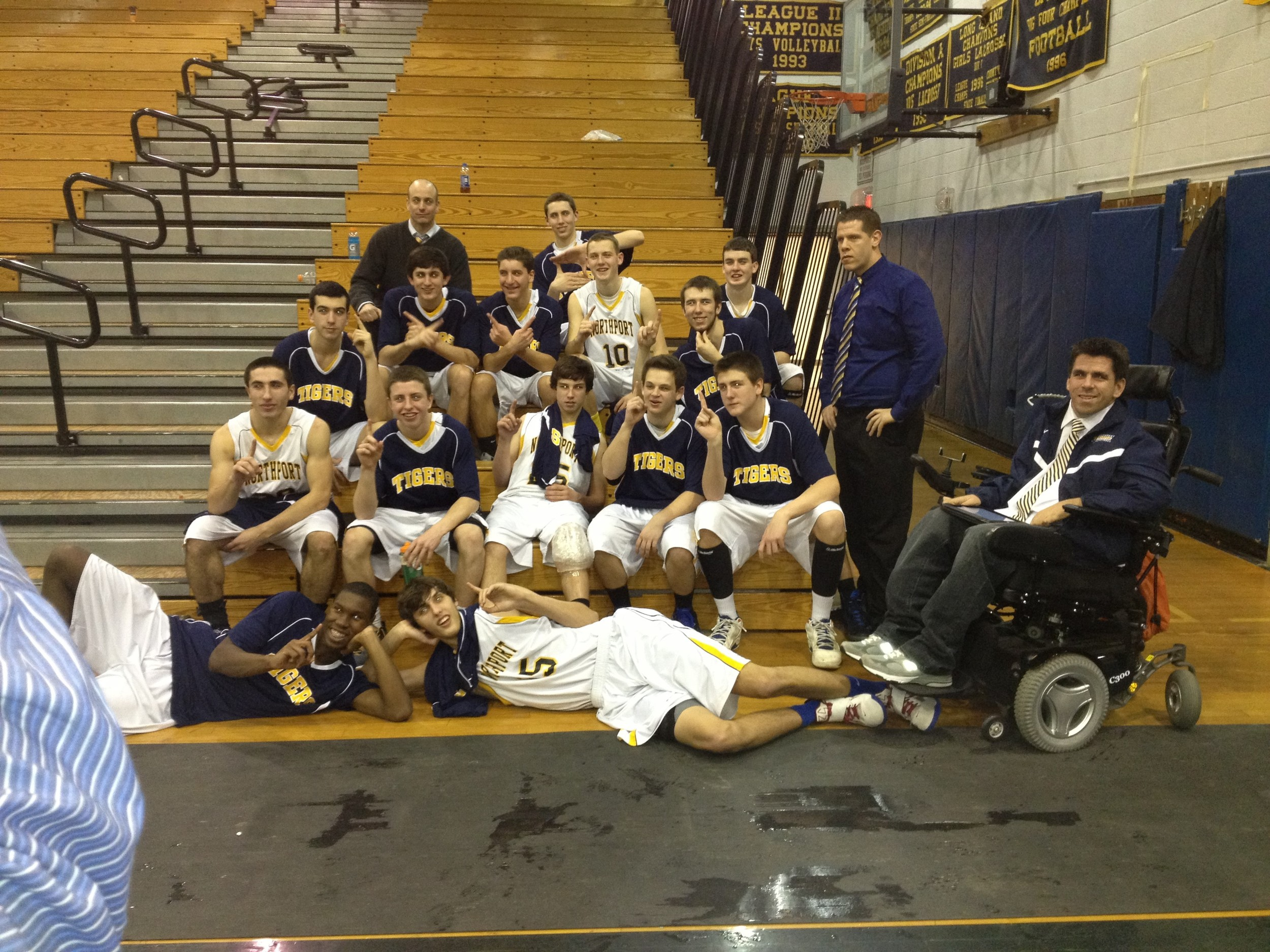 Assistant coach for the Northport varsity boys basketball team, Tim Dunne, right, poses for a picture with the 2012-2013 team, which went on to win a Long Islander championship.