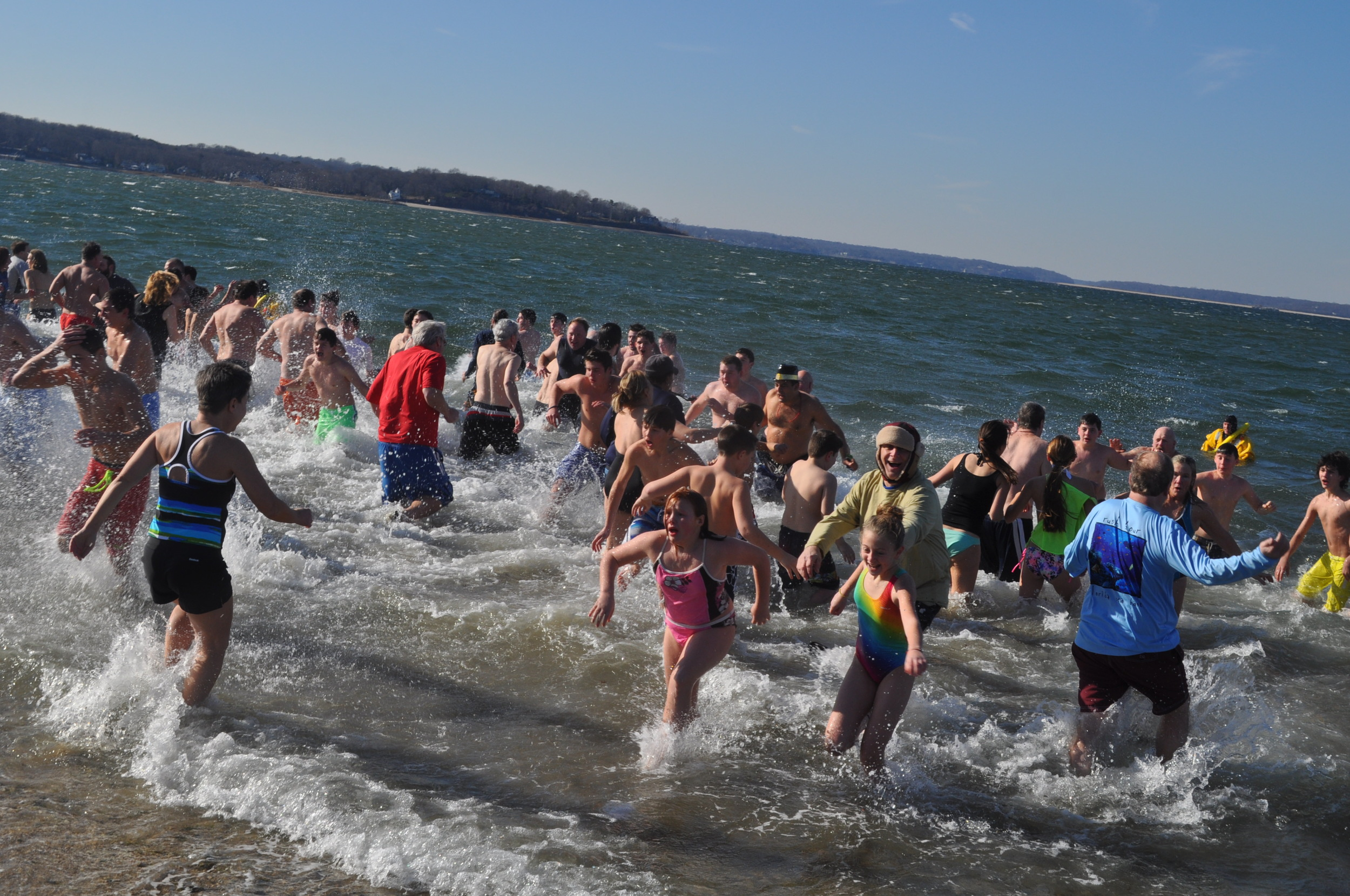 Run for warmth! Some of the hundreds race for the shore after christening 2015 with a frigid dip at Steers Beach.