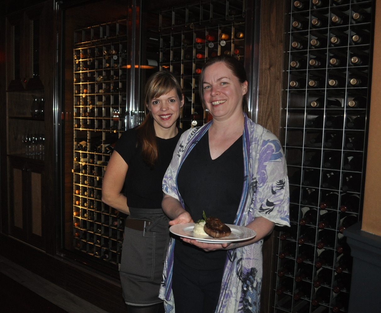 Waitress Justine Stokes and manager Kelly Danek present Red's organic filet mignon and the impressive wine rack, a focal point of the restaurant's dining room.