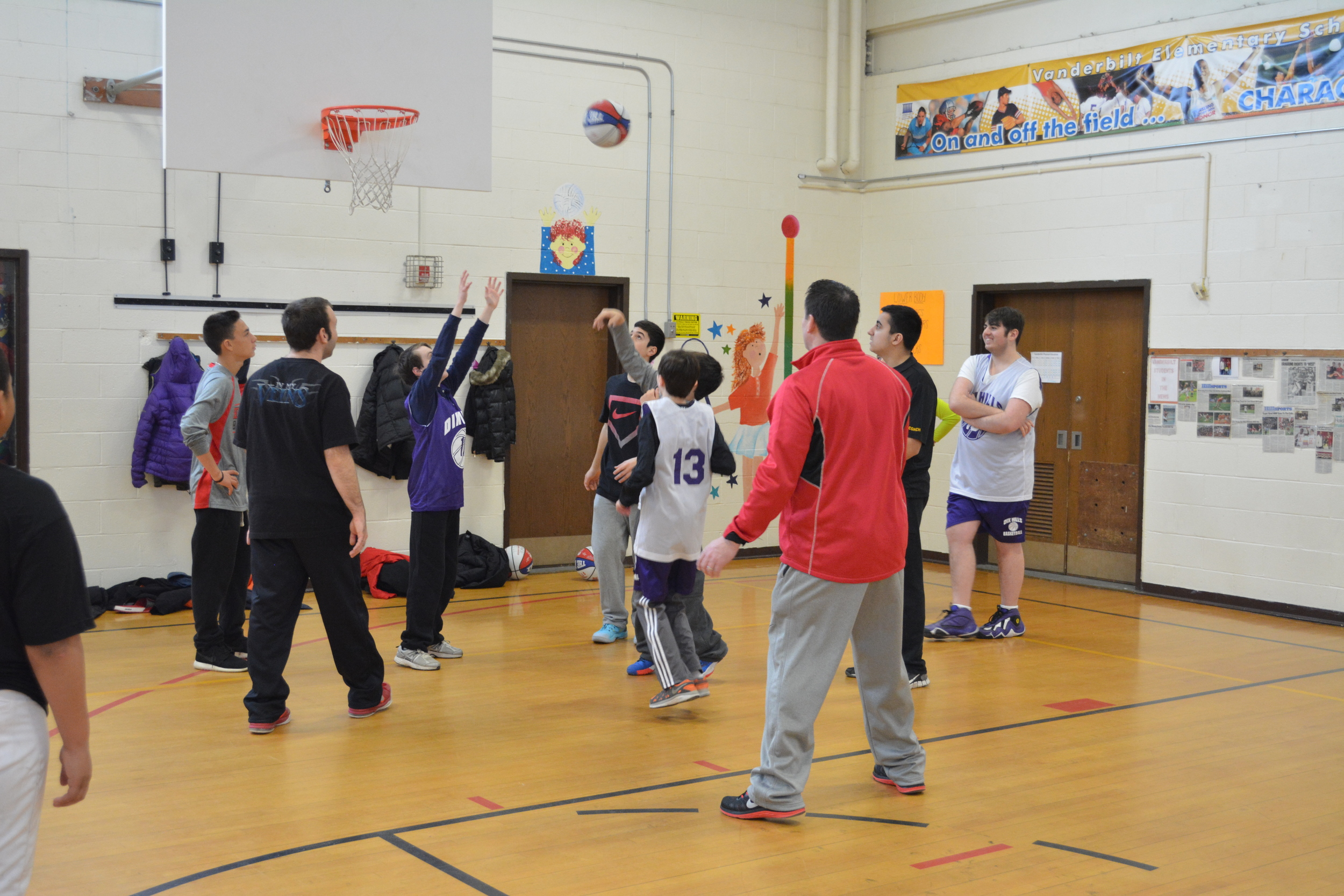 On Saturday morning, several members of the Half Hollow Hills High School East basketball program volunteered their time to work with the kids of Dix Hills Basketball Association's Challenger Program. Inset, a team huddle caps of the day with Michael Pliskin, right, one of the program's coaches, leading the wrap-up.