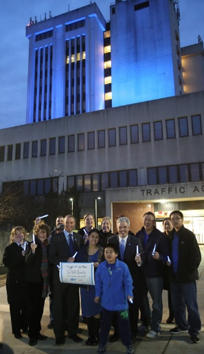 Nova and Zen Shek stand between Legislator Steve Stern and County Executive Steve Bellone, along with autism advocates in front of the Dennison building, lit up blue.