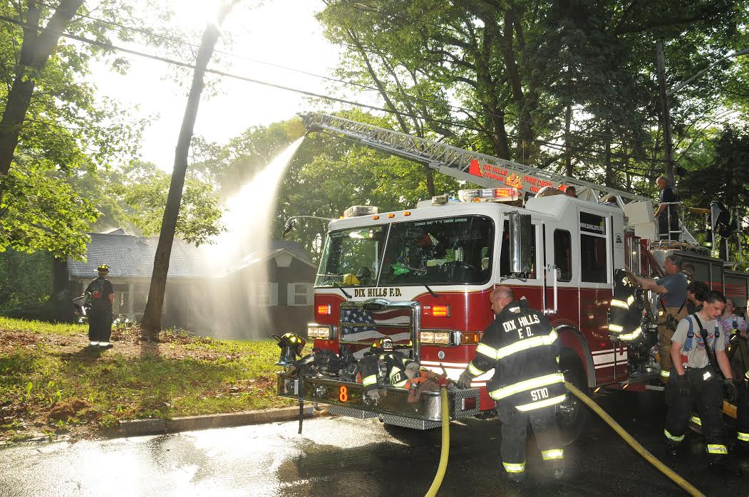 A fire truck douses the home, which town officials said is expected to be the subject of a blight hearing on Tuesday, June 2. (Photoby Steve Silverman)