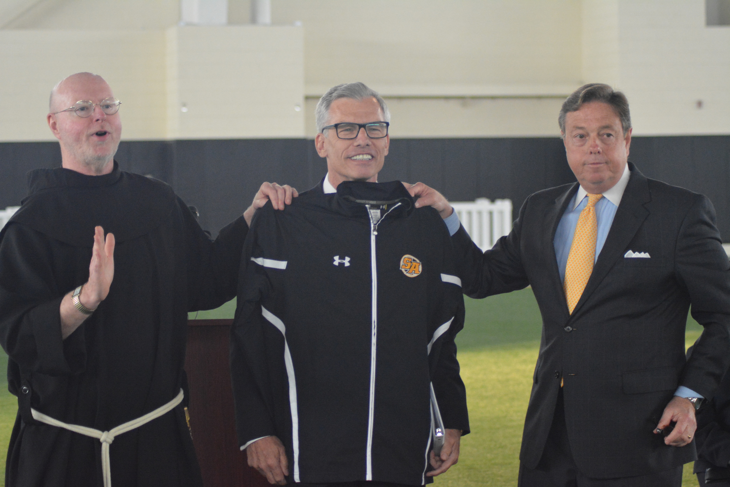 """St. Anthony High School's Principal Brother Gary Cregan, left, and Director of Development Don Corrao, right, present James Metzger, center, with honors after announcing hedonated the """"lead gift"""" towards construction of the James C. Metzger Stadium, which school officials hope to complete before the year's end."""