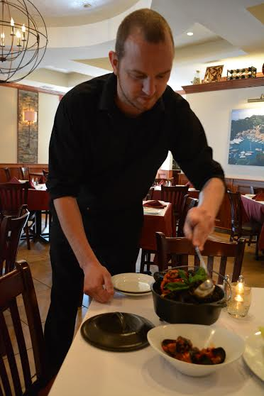 Longtime server Timothy Grill - the first hired when Porto Fino opened three years ago – dishes out Angry Mussels during a Monday afternoon visit.