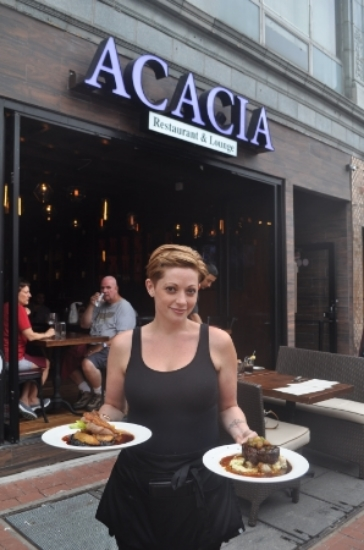 A member of the Acacia's staff displays Long Island Duck Breast and the 8 oz. filet mignon outside the restaurant, located at 371 New York Ave. in Huntington village.