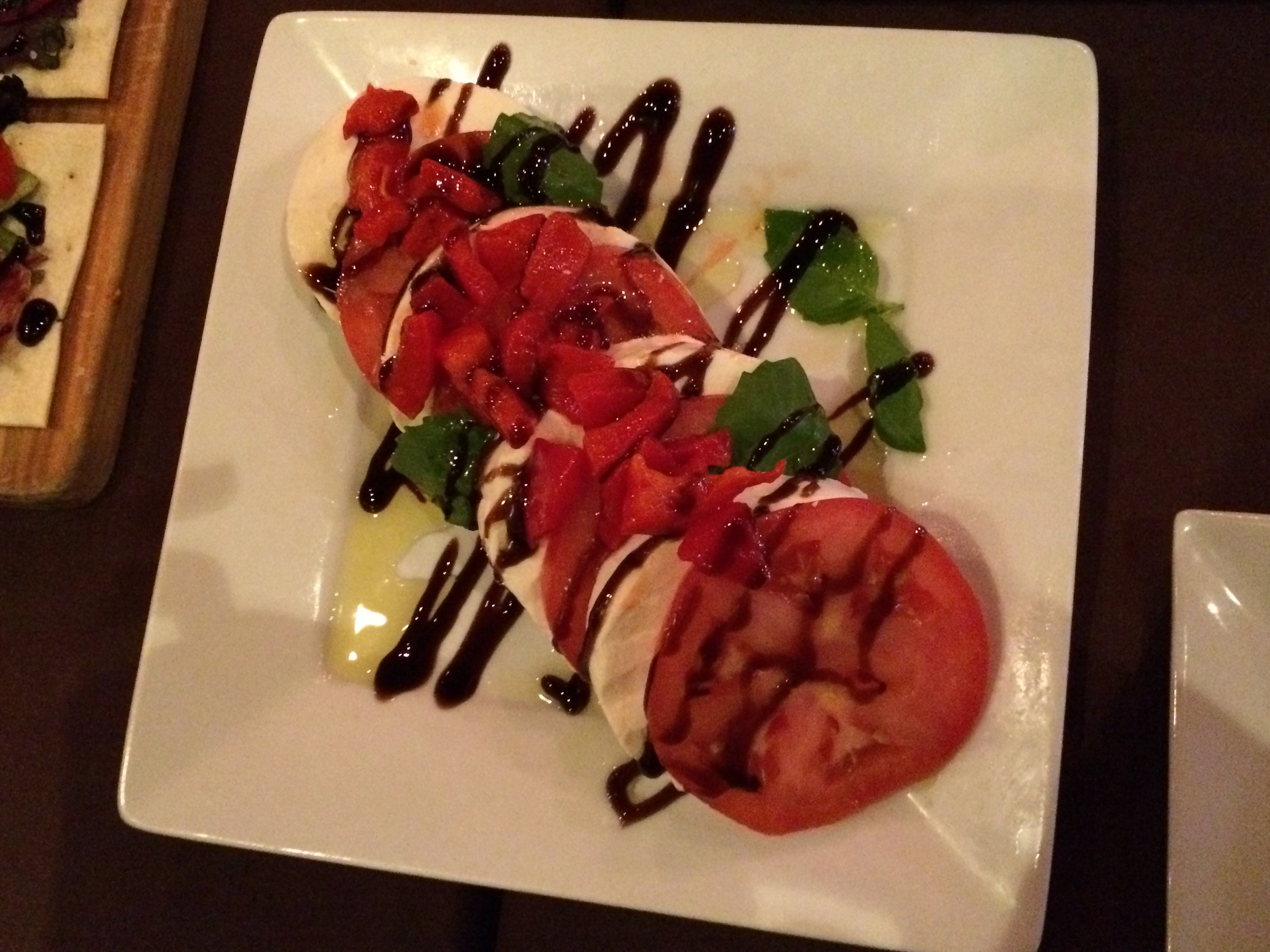 A fresh mozzarella platter with sliced tomato, roasted red peppers and a balsamic glaze drizzle.