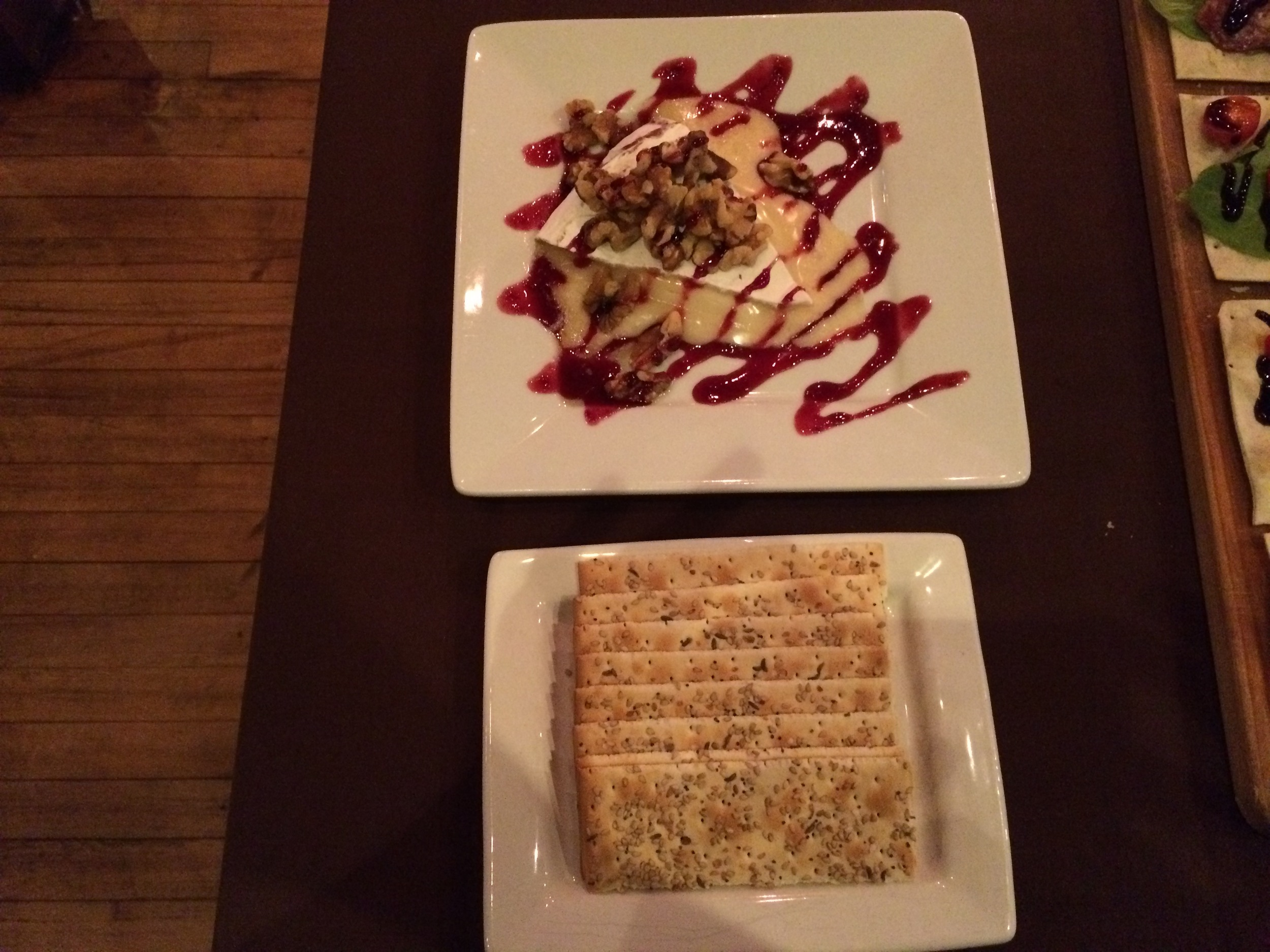 Warm brie with walnuts and berry preserve served with flatbreads.