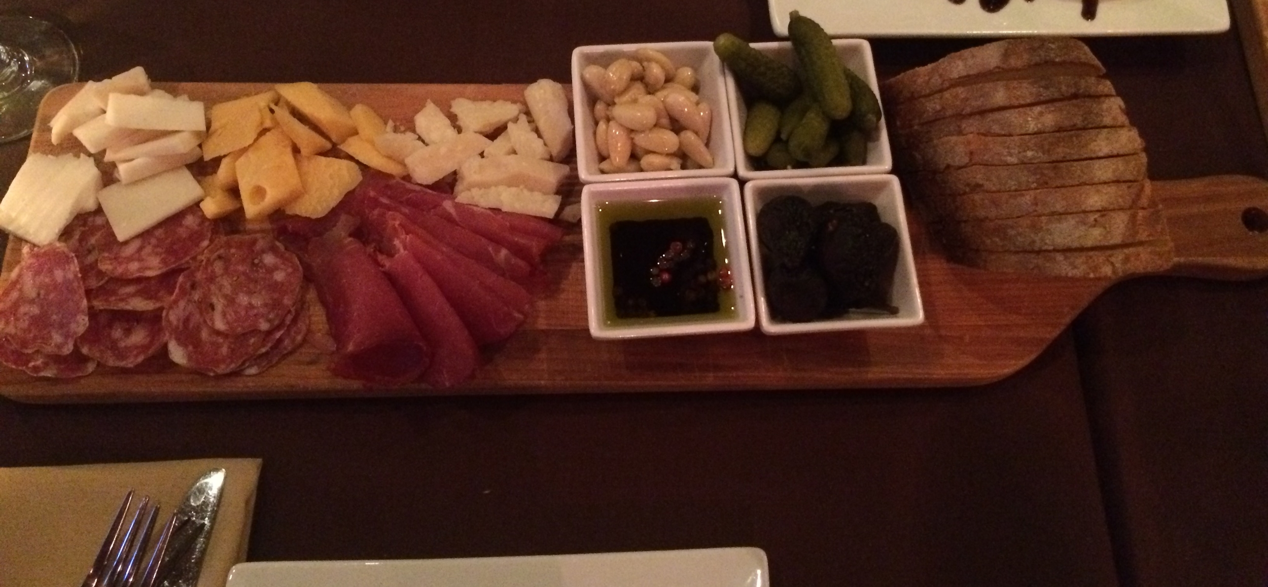 A delicious cheese and meat board, piled with a variety of delectable offerings.