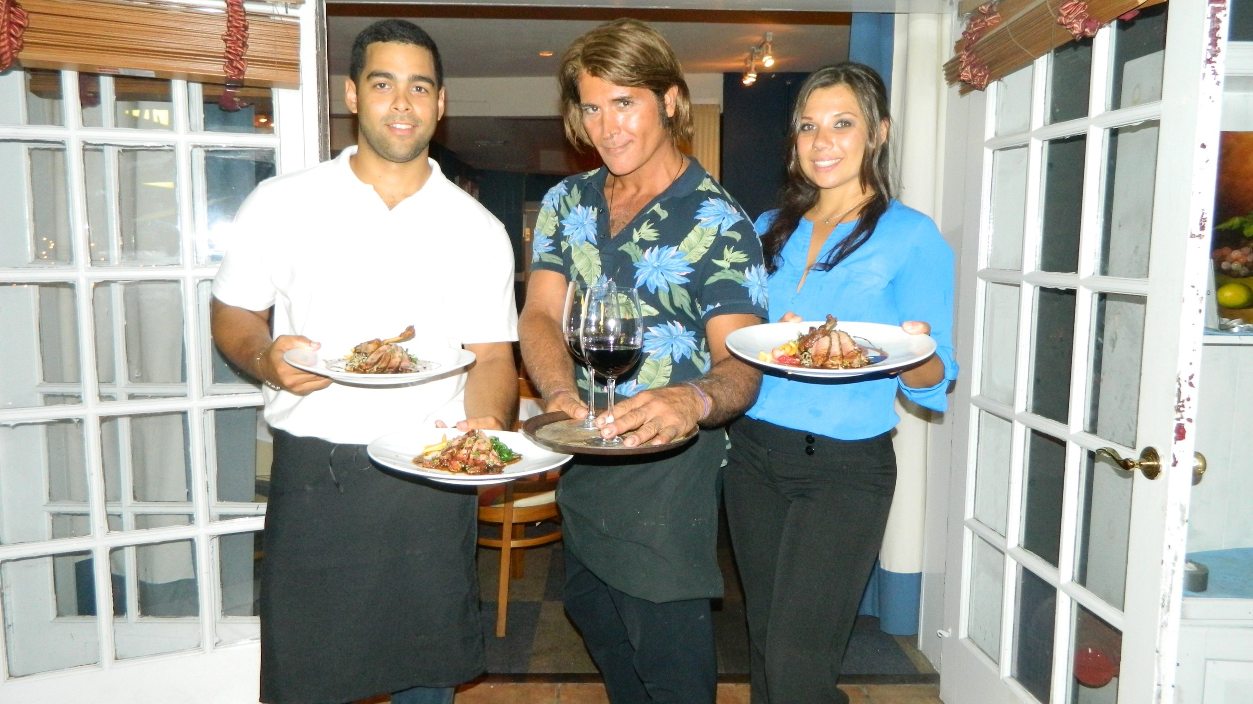 Manager John Angrisani (center) with Christian Feliciano and Courtney Handel, presenting duck with Americano wine.