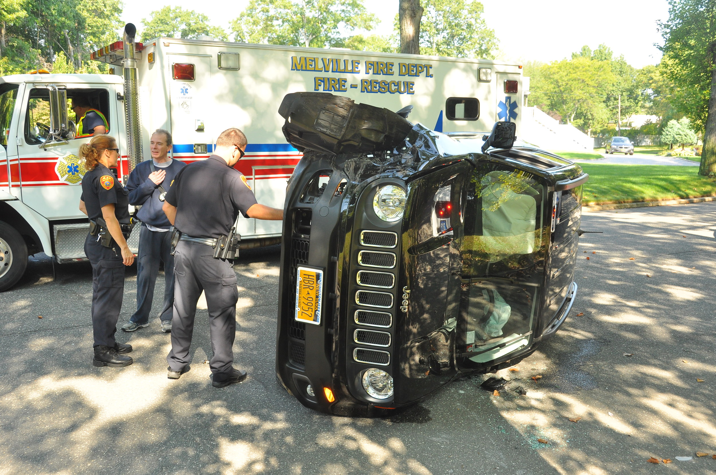 Melville Fire Department and Suffolk police work on a black Jeep Patriot Saturday morning after the driver struck a tree on Wintergreen Drive and the vehicle overturned. Photo by Steve Silverman