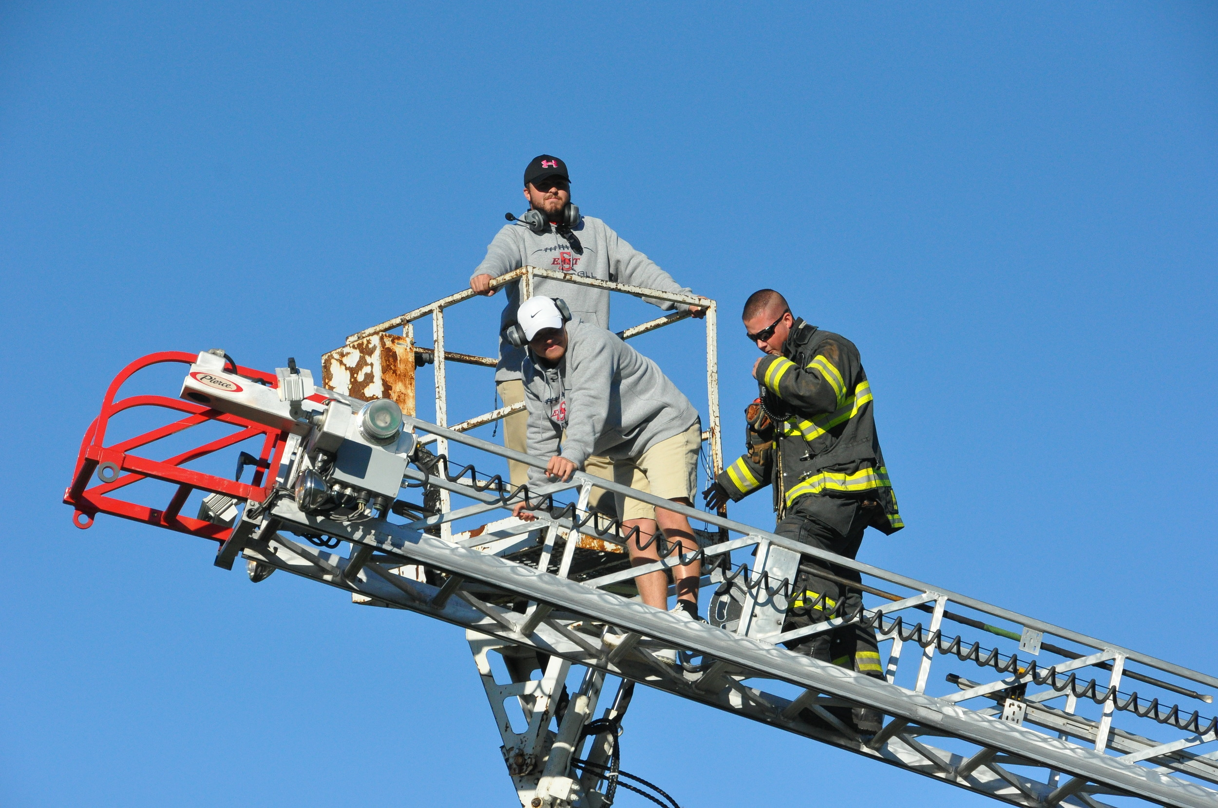 Dix Hills firefighter Matt Stio assists Tyler O'Neill, a Smithtown East football coach, after a bucket truck malfunctioned, leaving O'Neill and coach Tim Kopiske stranded 30 feet in the air Saturday afternoon after Half Hollow Hills High School East's homecoming game. (Photo by Steve Silverman)