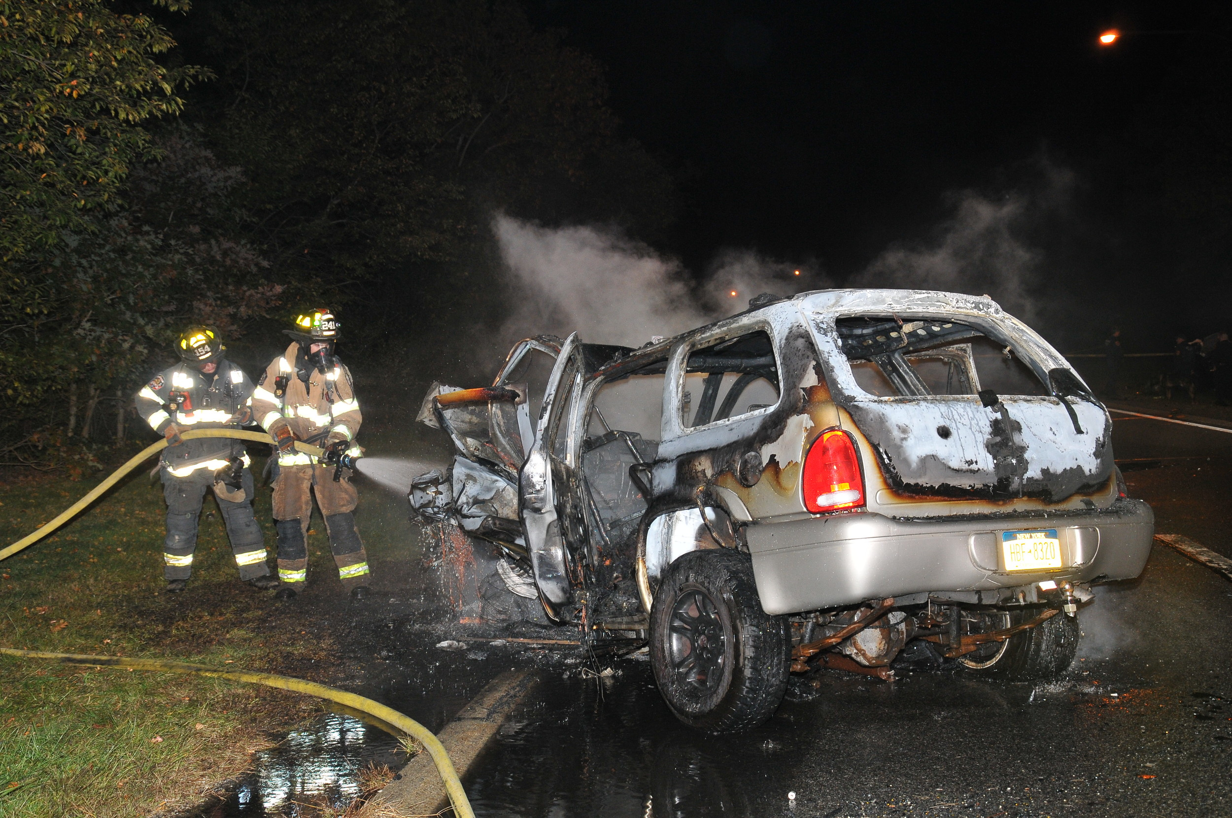 Dix Hills Firefighters extinguish a SUV that was involved in a wrong-way crash that killed two people on the Northern State Parkway in Dix Hills on Oct. 20. Photo credit: Steve Silverman.