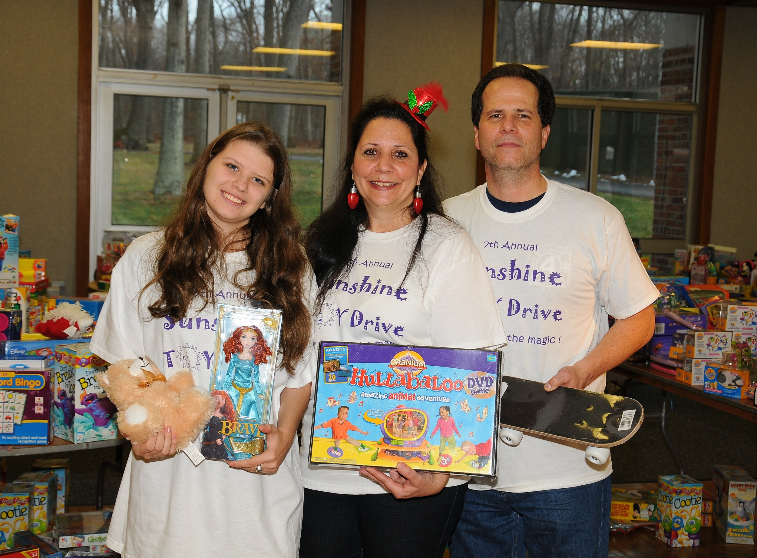 The Plumitallo family stands among the many toys donated to their 7th   annual Sunshine Toy Drive while at the Dix Hills Fire Department   Headquarters. Pictured from left are Victoria (Sunshine), Hope and Mike   Plumitallo.