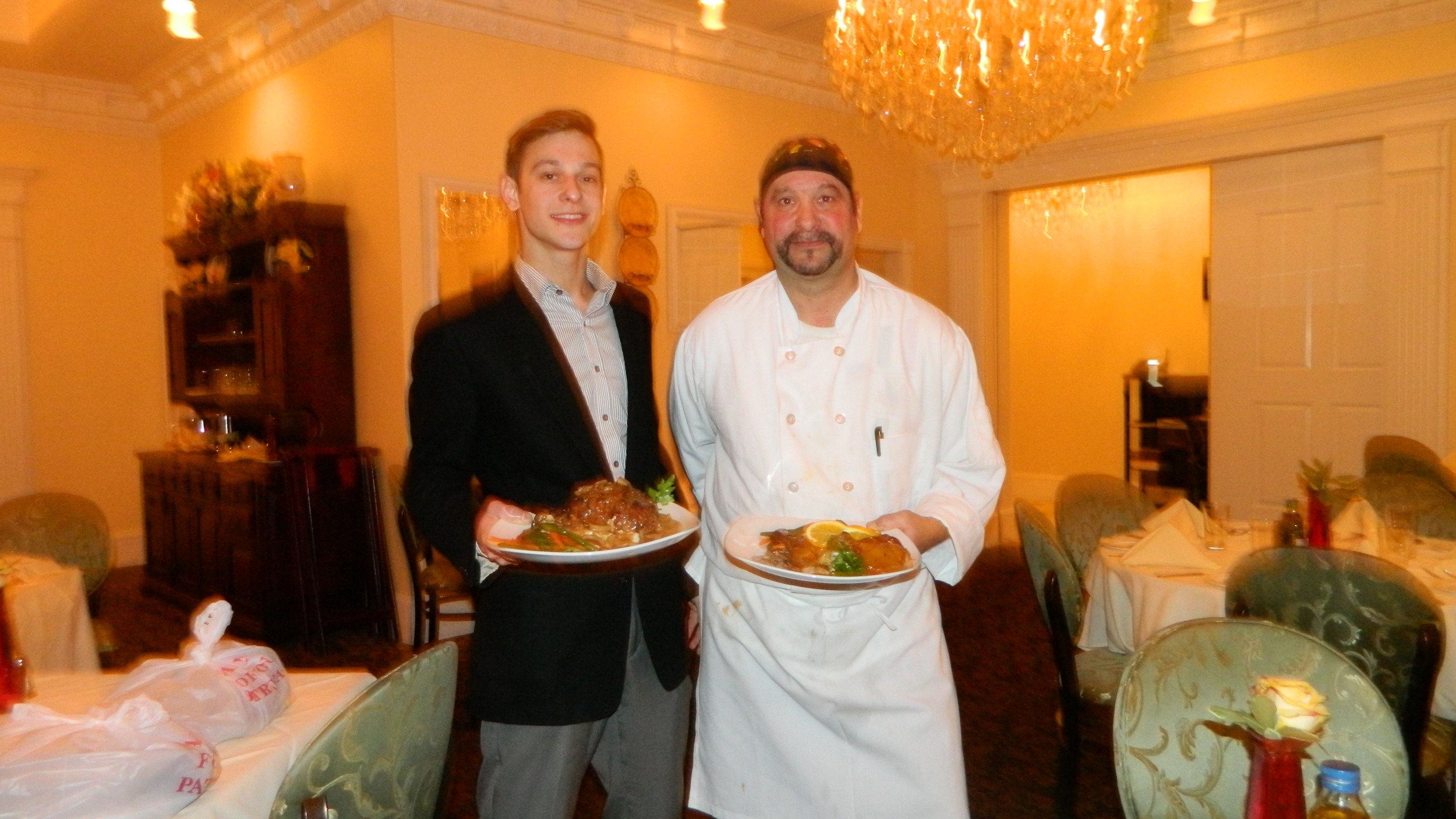Cinque Terre owner, Chef Anthony Page, right, and son, Anthony, present crispy duck and stuffed pork chop entrees.