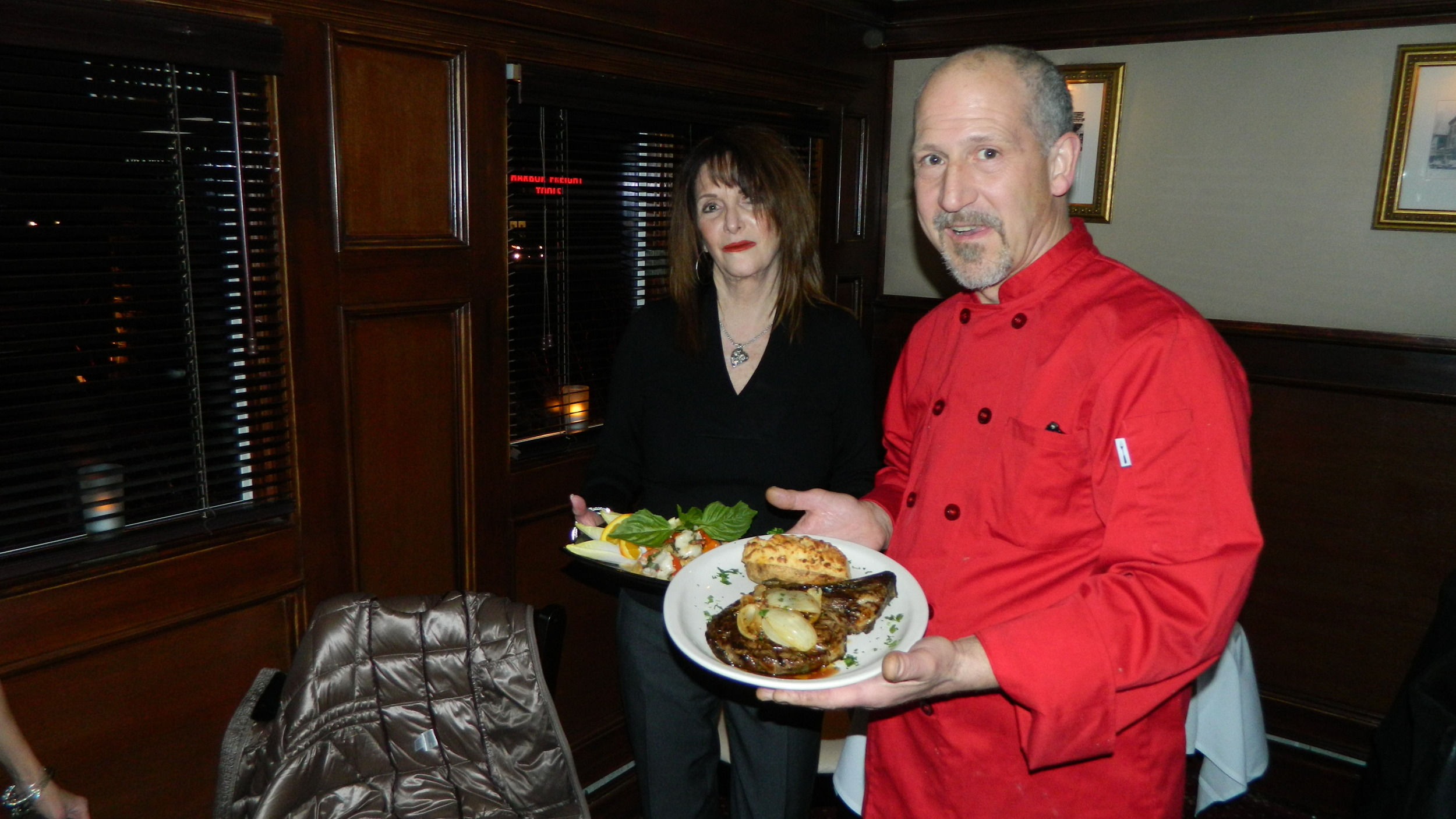Clubhouse Co-owner Cassandra Bies and Chef Charles Labartino present bone-in ribeye steak and Chilean sea bass with shrimp entrees.