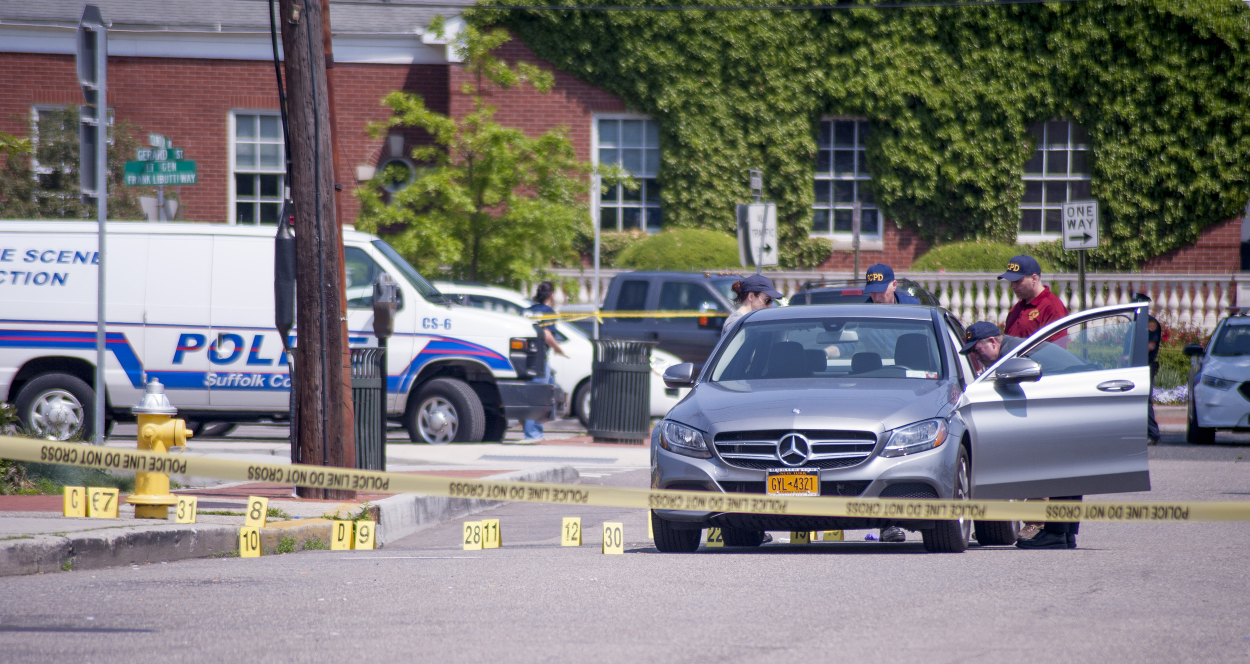 Suffolk police investigate the scene on Clinton Avenue in Huntington village where they said a man was found lying in the street early this morning next to a Mercedes with its driver's side door open. The man was later pronounced dead. (  Long Islander News photo/Jano Tantongco)