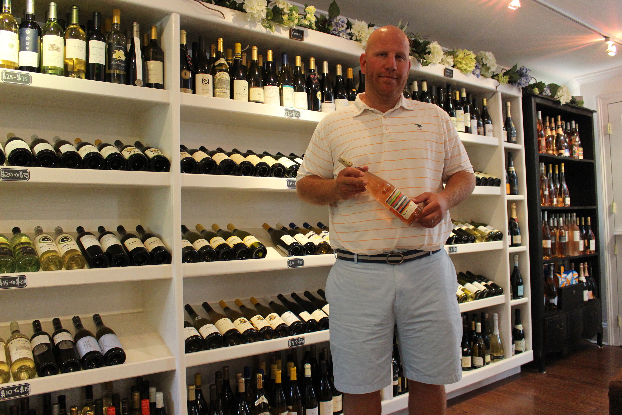 Andrew Robinstein, owner of Cold Spring Harbor Wine Shoppe, holding a popular and rare bottle of Pinot Noir California Red Car.