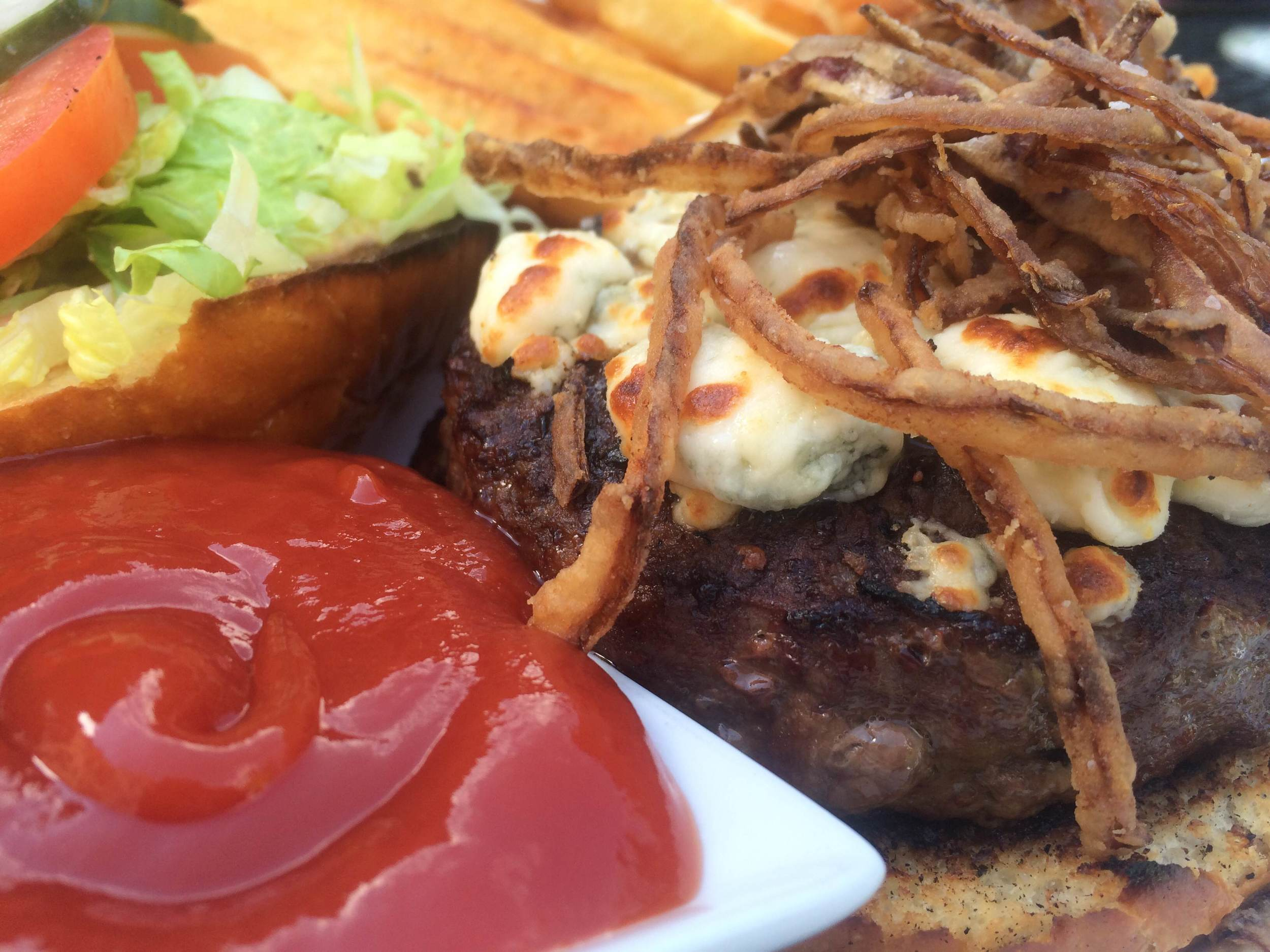 The Kobe short rib beef burger at Bistro 44 is served on a brioche bun with Stiton bleu cheese, Applewood bacon, frizzled onions, shredded lettuce, and with French fries for $14.50 on the lunch menu.
