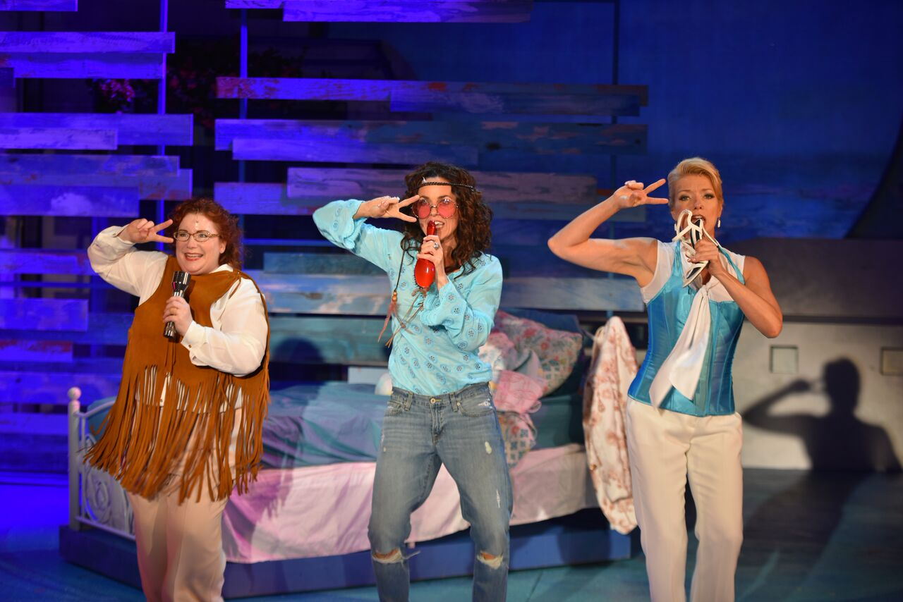 """Singing """"Dancing Queen,"""" actresses Robin Lounsbury (as Rosie), Michelle Dawson (as Donna) and Heather Patterson King (as Tanya) embody girl time by playing dress up and using a shoe, a flashlight and a hairbrush as their microphones."""