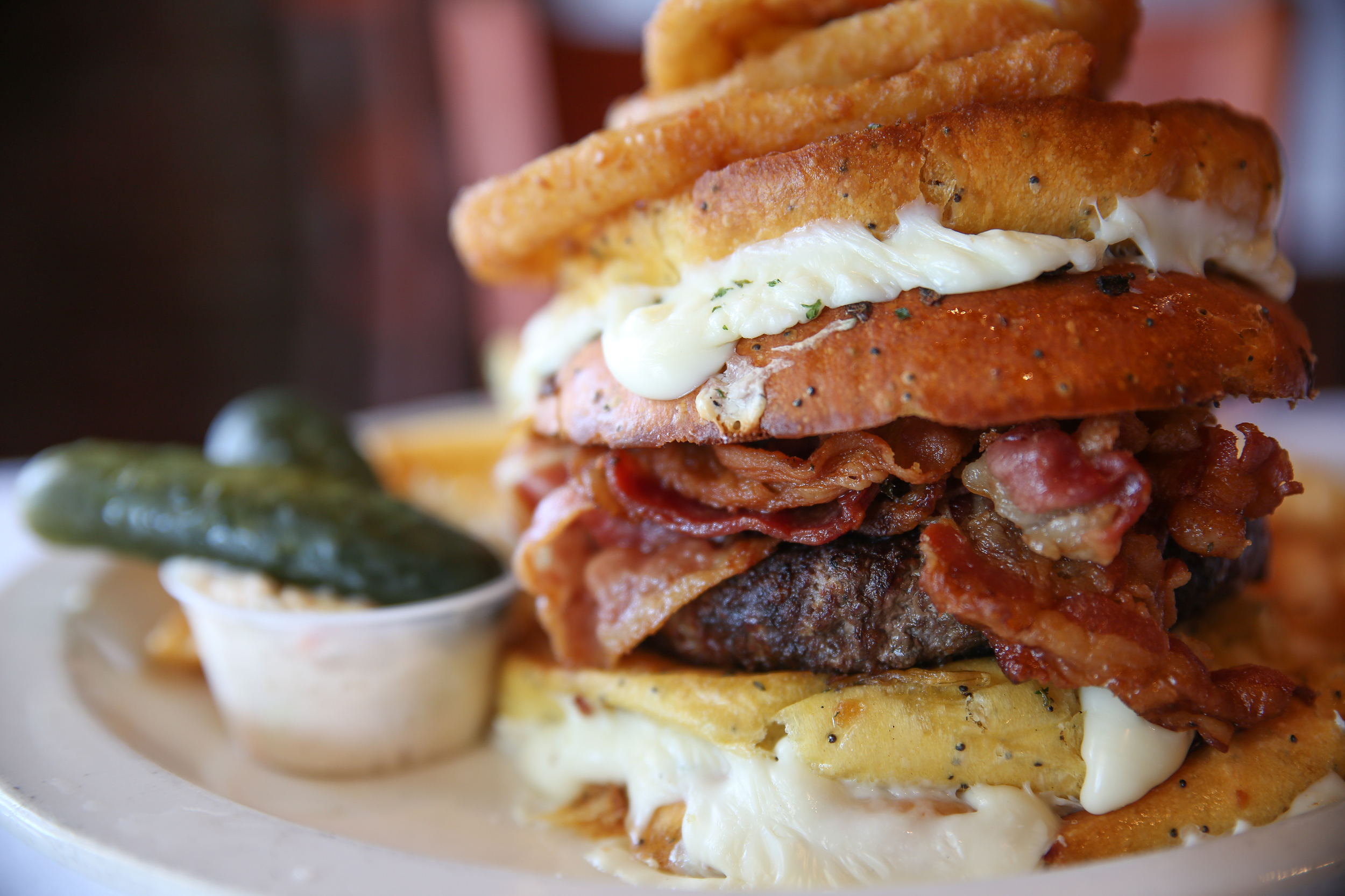 """Chef Frank calls the The Bacon Belly Buster burger a """"challenge,"""" boasting two Texas toast grilled cheese sandwiches instead of buns, surrounding a beef burger with bacon."""