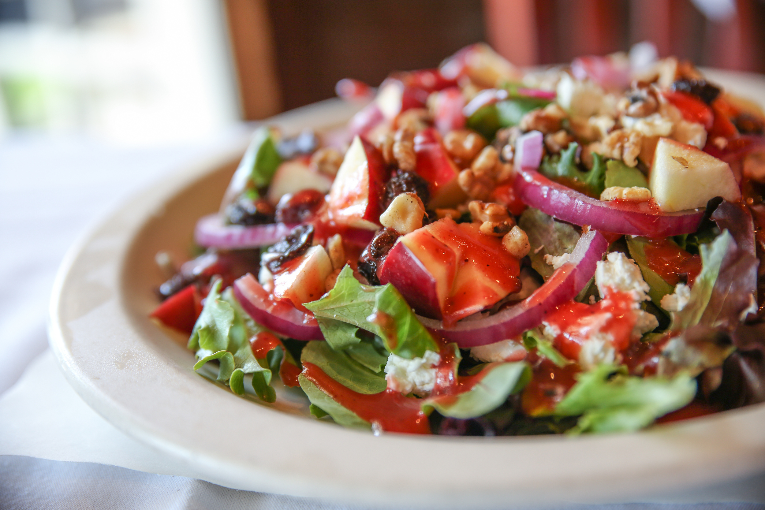 The Goat Cheese and Apple Salad goes toe-to-toe with the generous entrees, bringing the richness of goat cheese, balanced with toasted walnuts, raisins, lettuce and red onions topped with a light and springy raspberry vinaigrette.