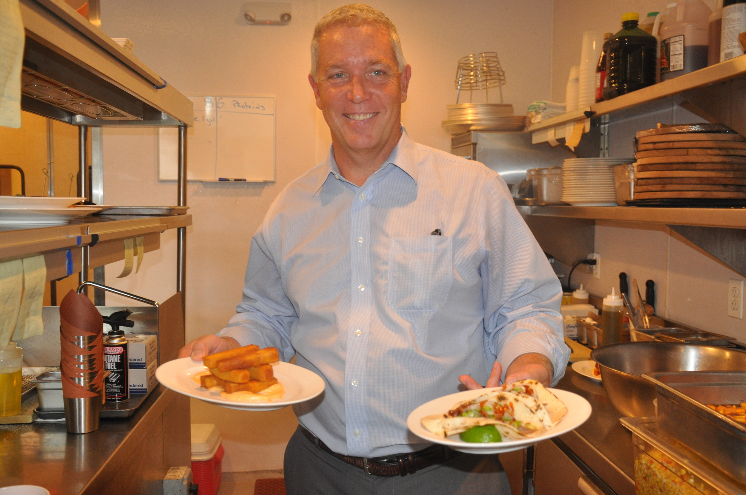 James Olsen, general manager of Sandbar in Cold Spring Harbor, is all smiles holding delicious chickpea fries, left, and duck tacos appetizers.