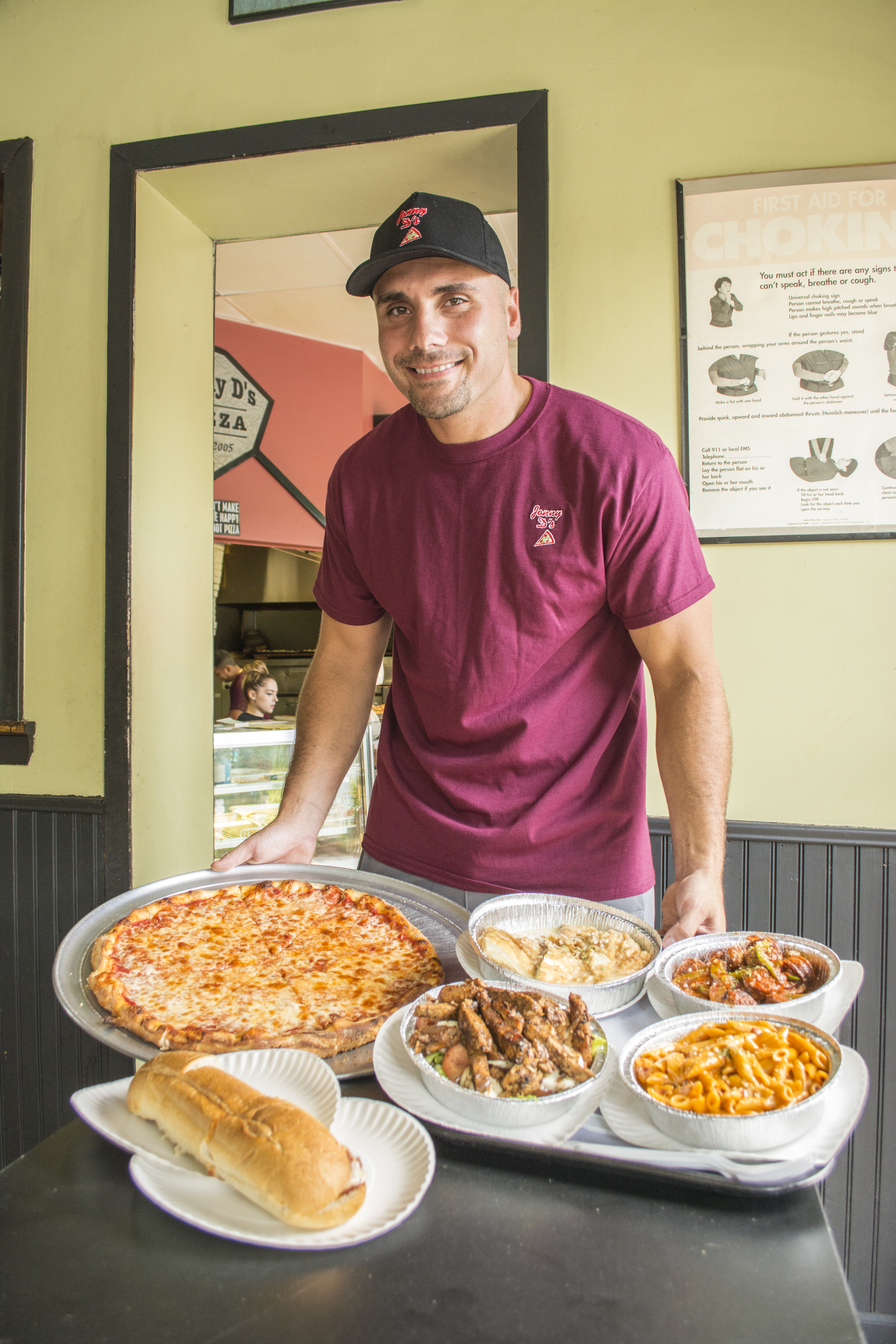 Jonny Dawson, owner of Jonny D's Pizza, shows off some of the pizzeria's offerings. From left: a regular cheese pie; chicken parmesan hero; salad with grilled chicken; chicken francese; penne ala vodka; and sausage and peppers.