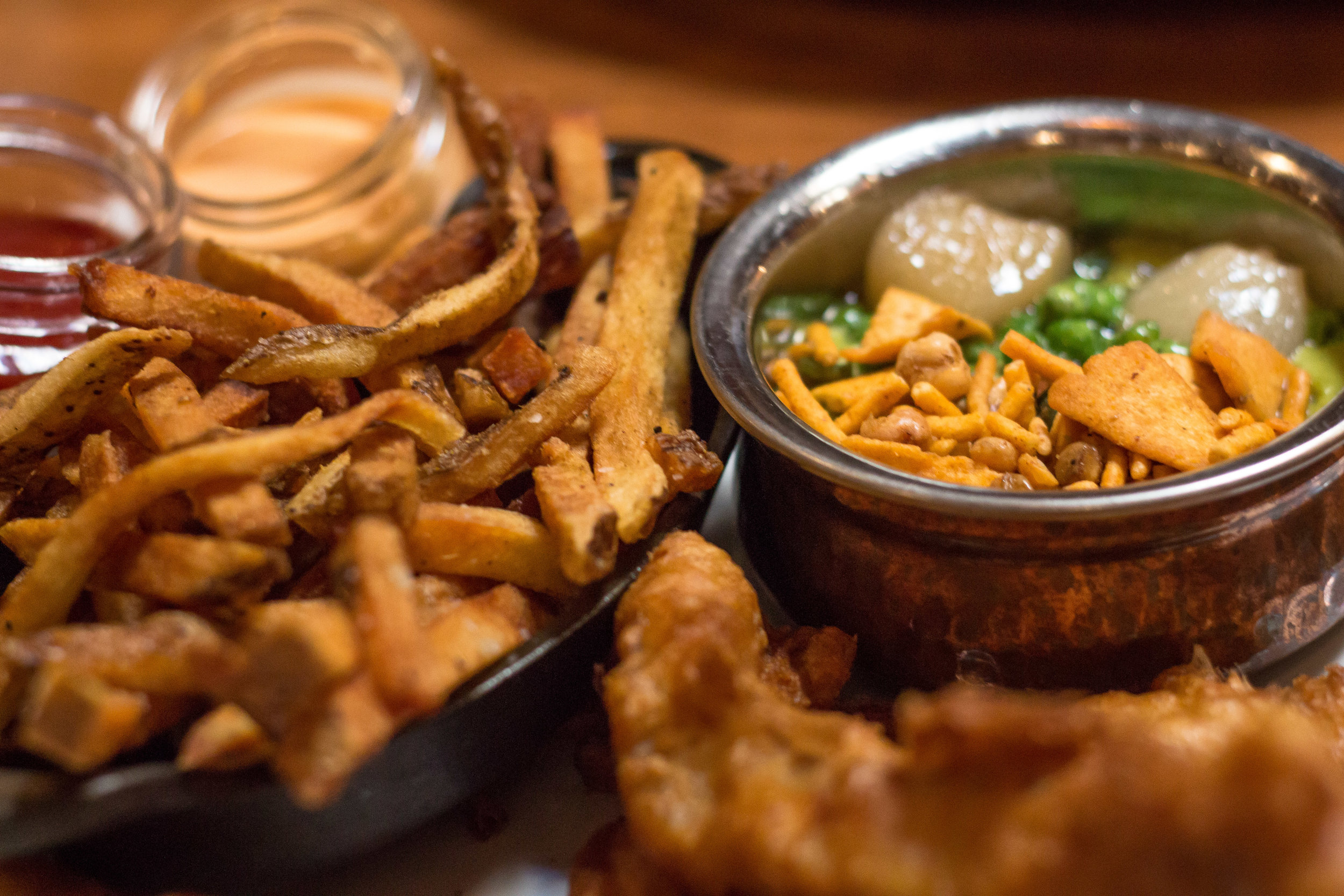 Montauk Fish and Chips Madras Tempura is a small feast of its own, featuring sides of mushy peas with pearl onions and curry fries, mixing flavors that run the gamut for a dish that pleases on multiple levels.