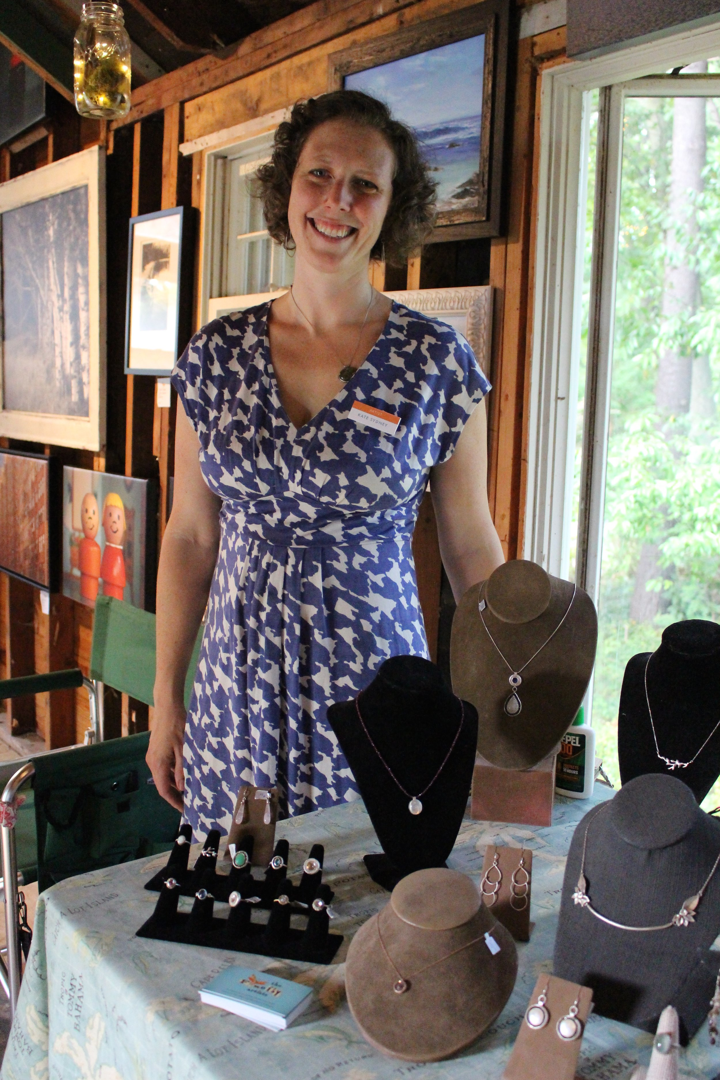 Long Islander News photos/Janee Law  Kate Gilmore, co-founder and managing partner of Firefly Artists, stands next to her table of jewelry at the Firefly Artists' pop-up gallery event that was hosted in Eatons Neck over the weekend.