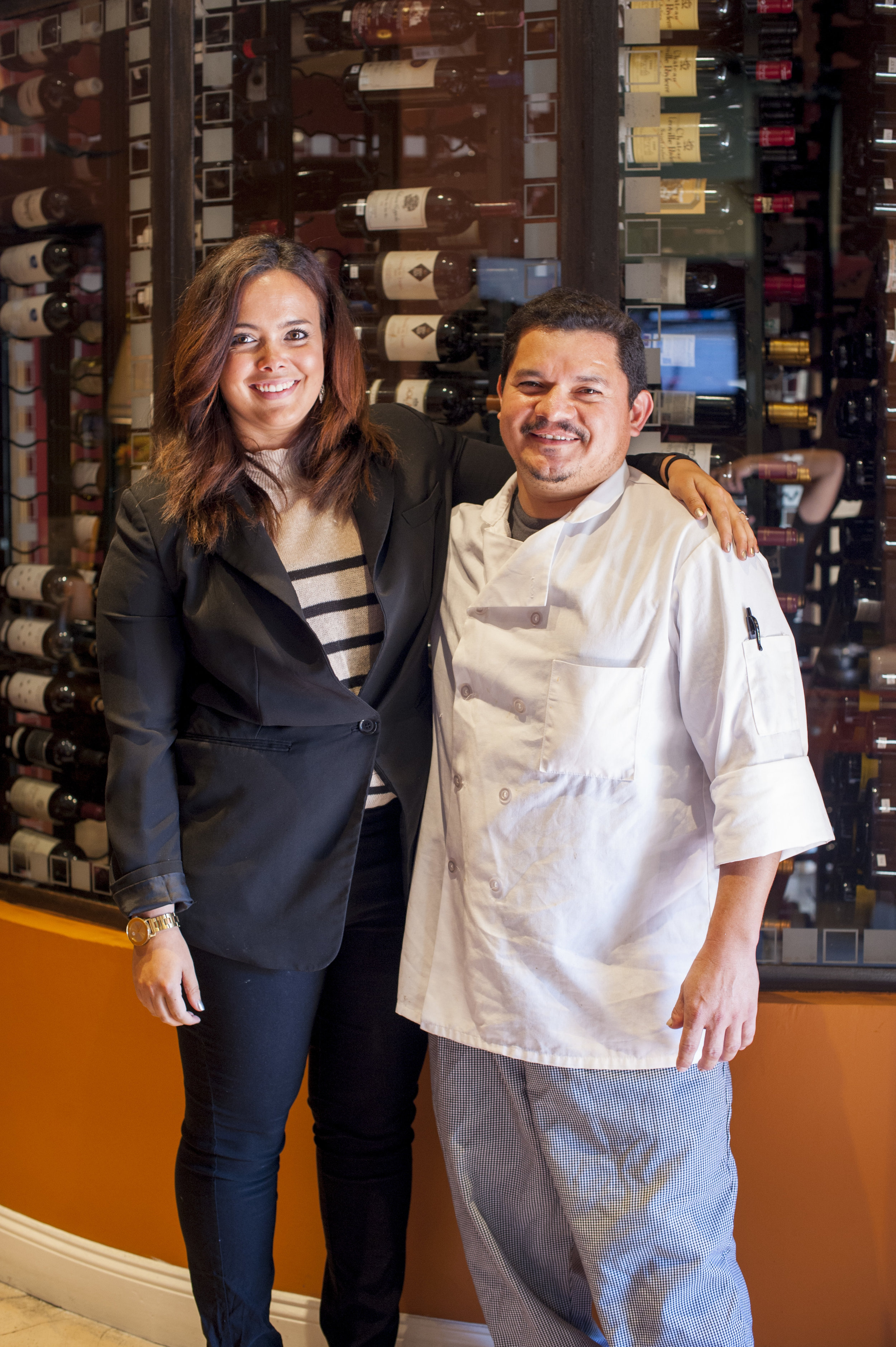 Mac's Catering Manager Leanne Gelish and Executive Chef Rafael Salmeron stand before the numerous wine offerings available the Huntington village steakhouse.