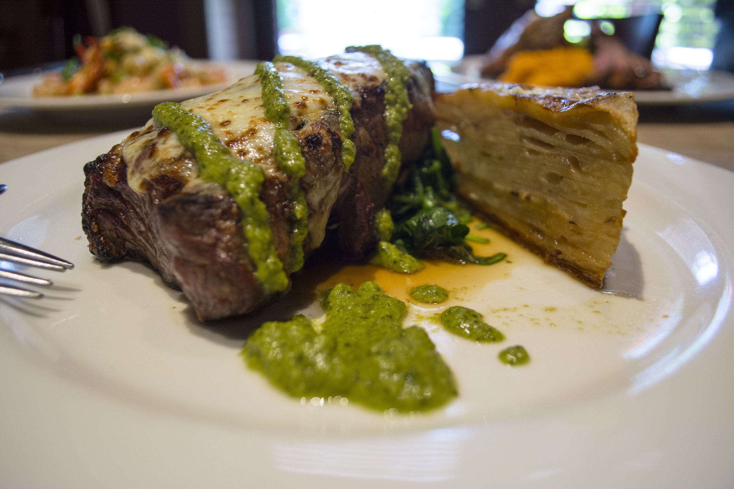 The creative, yet classic Dry Aged NY Strip steak is topped with cheese and chimichurri sauce paired with a side of potato au gratin and sauteed spinach.
