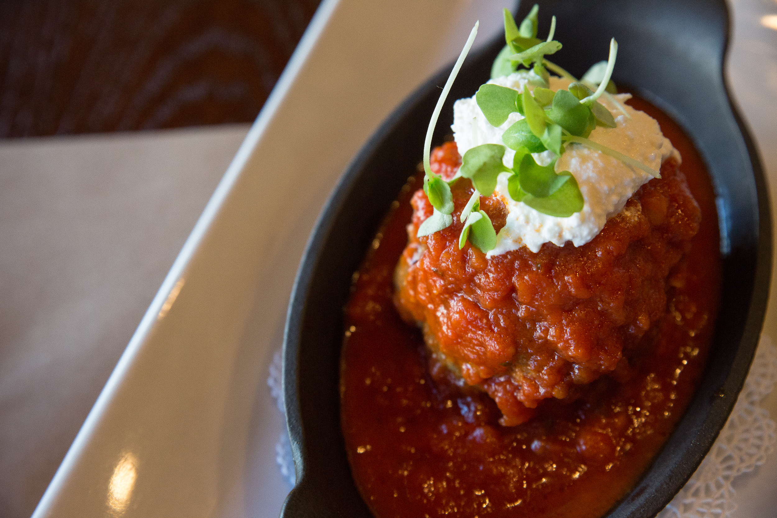The Polpetta housemade meatball integrates hearty seasonings, topped with a creamy ricotta, is an appetizer that takes one back home.