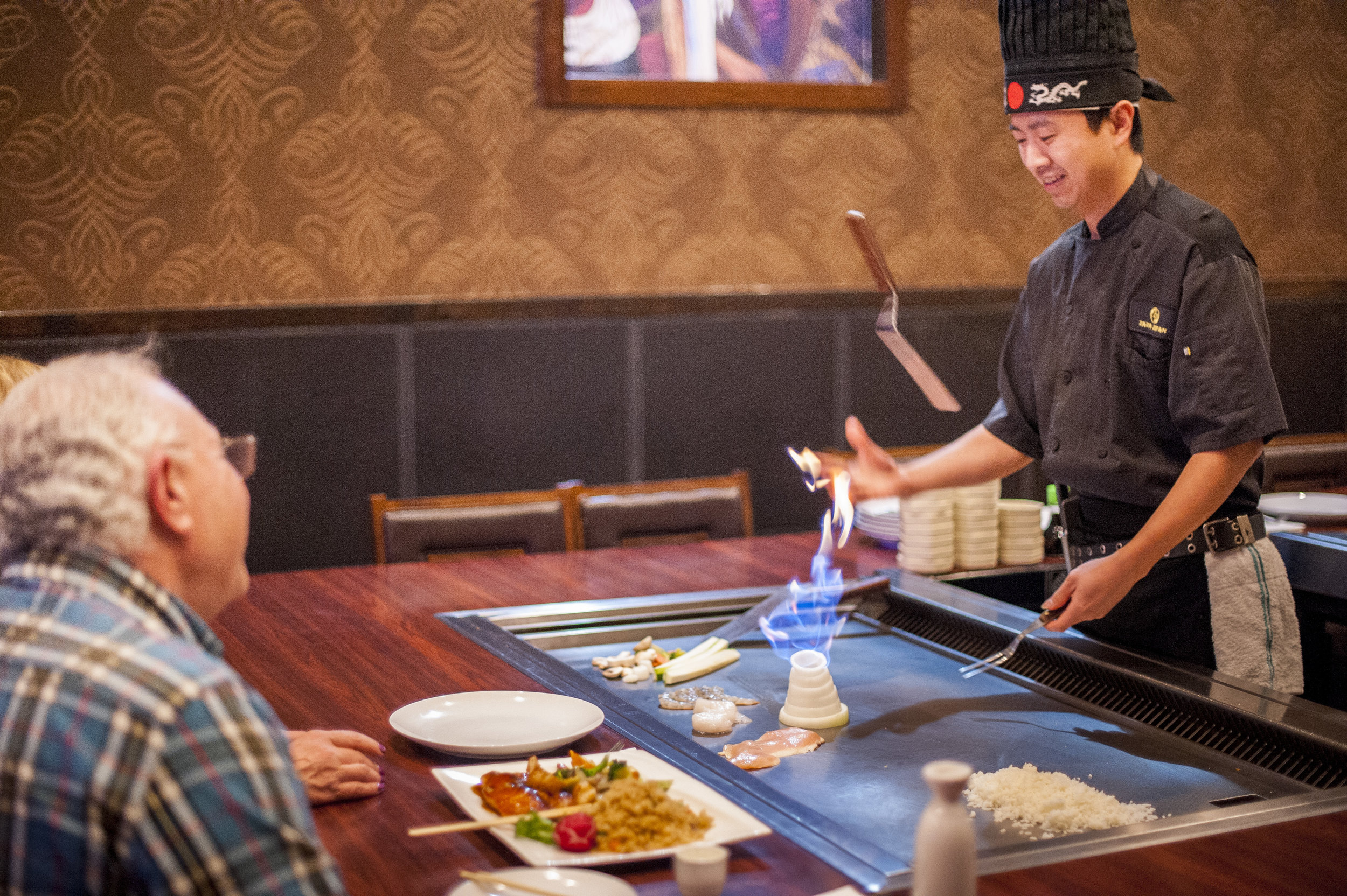 Keven Liu, head hibachi chef at Zaza Japan, wows patrons Hugo and Lisa Gasian with the roaring onion volcano as he prepares their meal.