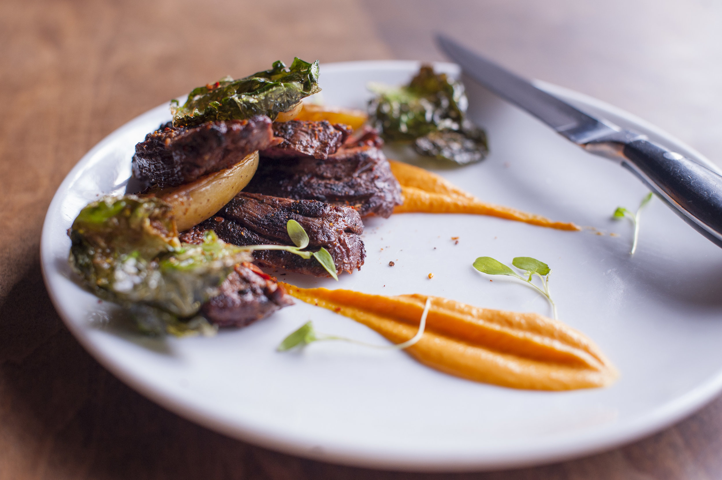 The Grass Fed Skirt Steak elegantly balances skirt steak rubbed with Japanese togarashi spice with a cooling vanilla carrot puree to provide a clean finish. It's also served with crispy brussel sprout chips and a side of fingerling potatoes.